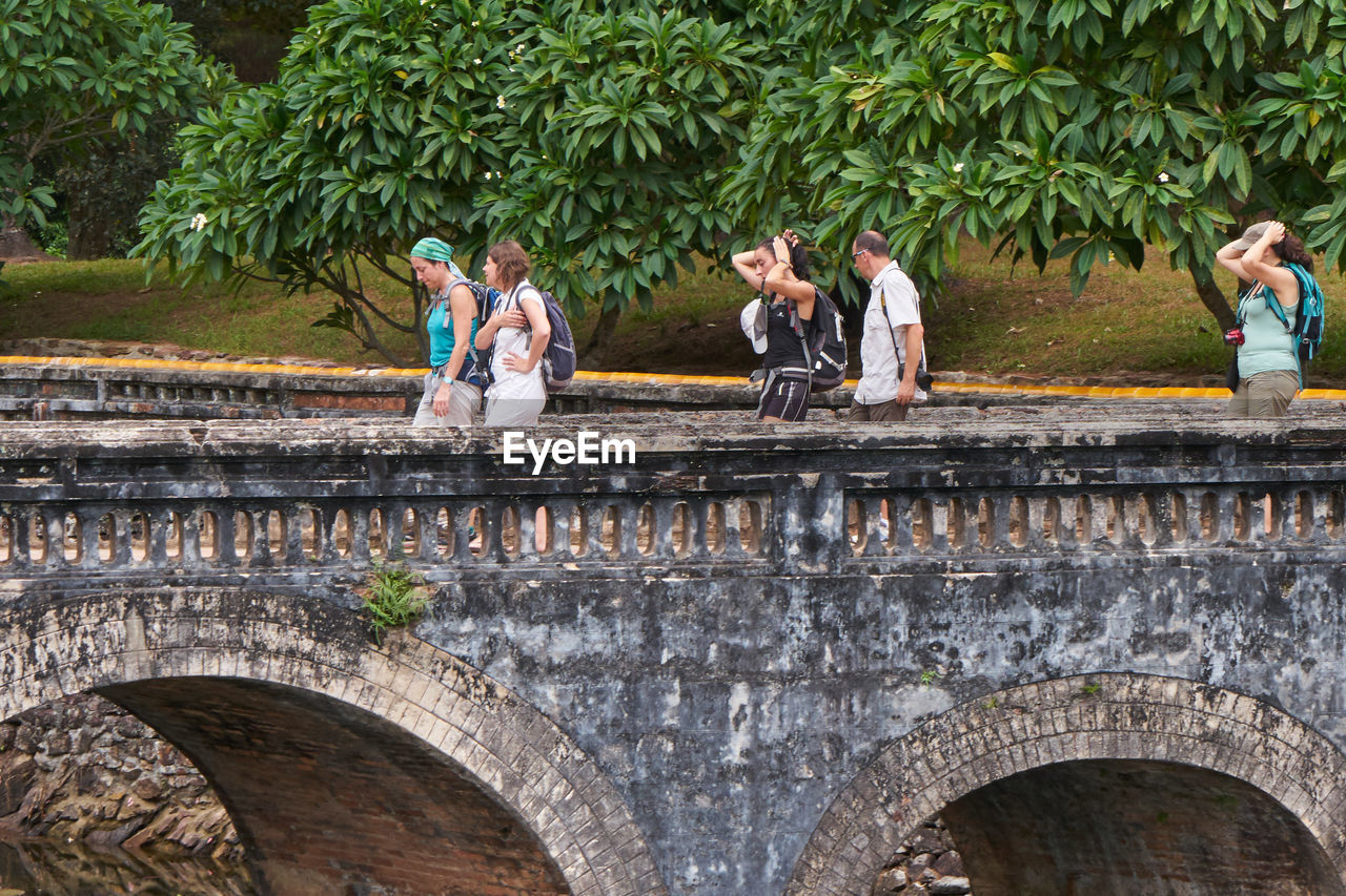 day, outdoors, bridge - man made structure, medium group of people, leisure activity, togetherness, tree, architecture, real people, travel destinations, built structure, nature, men, women, friendship, adult, people, young adult, adults only