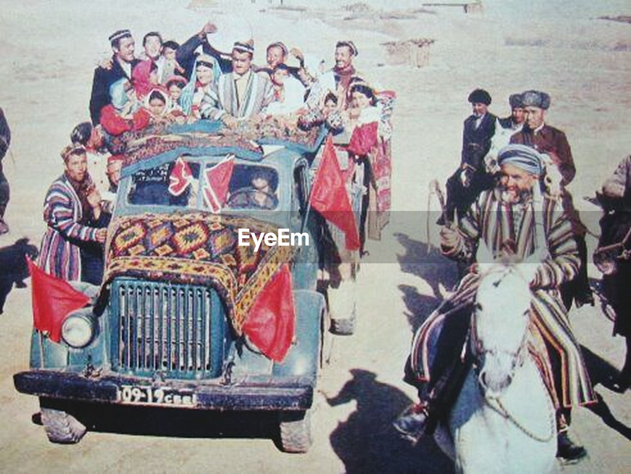 men, lifestyles, leisure activity, person, arts culture and entertainment, land vehicle, large group of people, transportation, high angle view, travel, art and craft, day, street, mode of transport, outdoors, sitting, casual clothing, art, medium group of people
