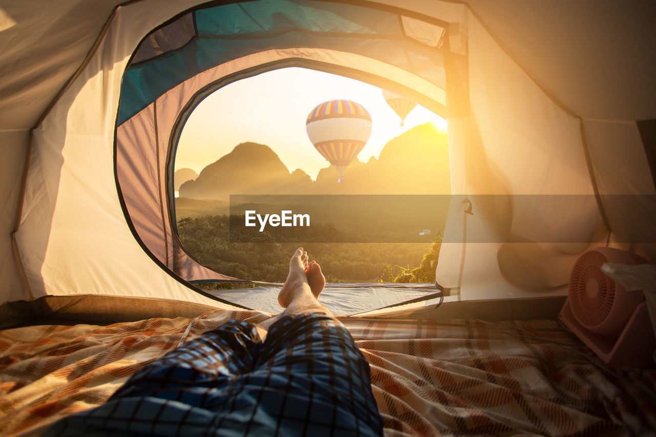Low section of man relaxing in tent during sunny day