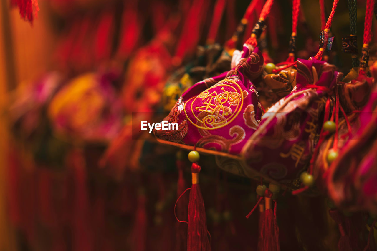red, close-up, art and craft, no people, selective focus, focus on foreground, hanging, creativity, decoration, market, craft, event, celebration, animal representation, for sale, representation, religion, festival, chinese new year