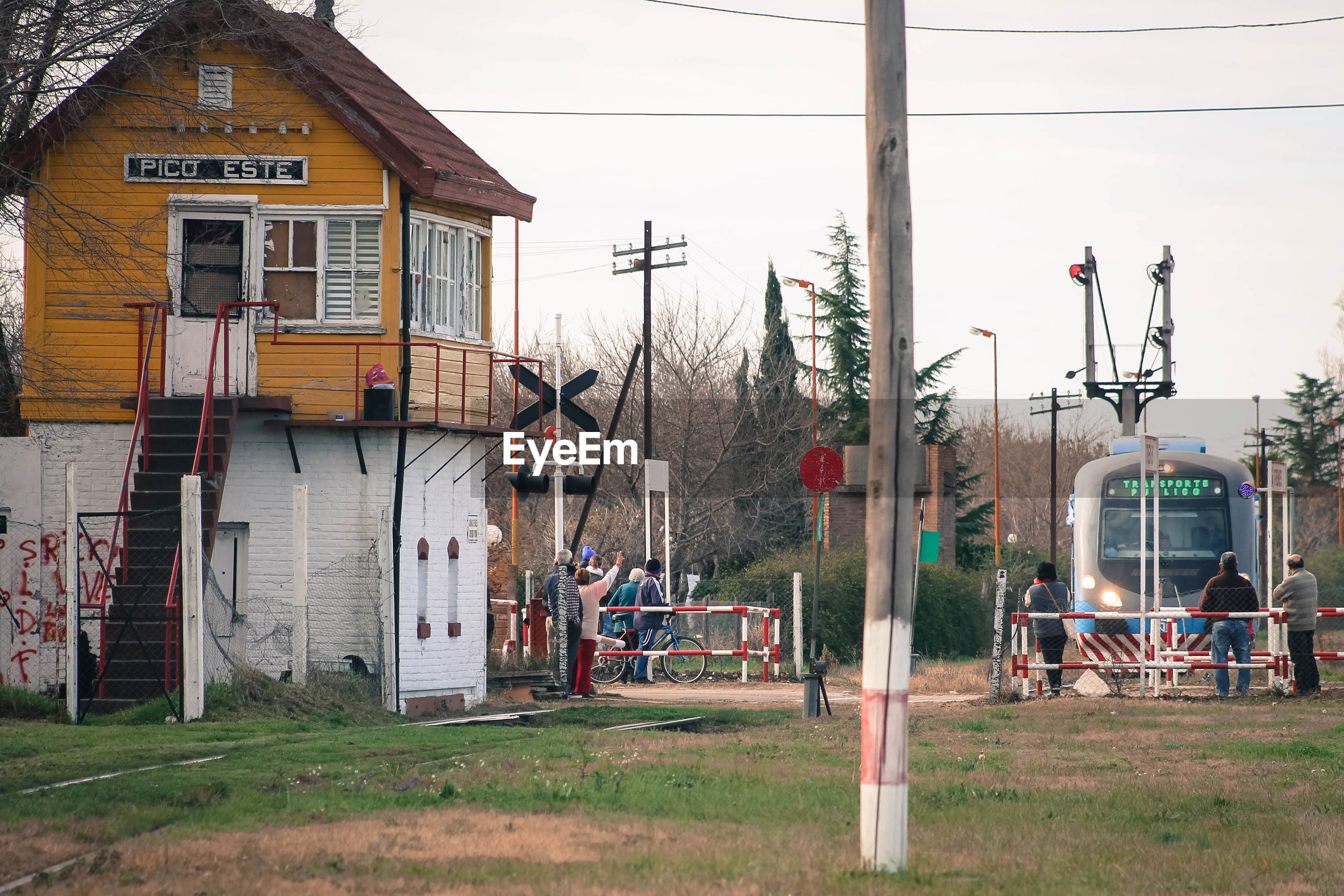 People by wooden cabin at railroad crossing