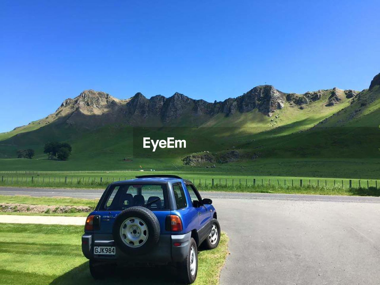blue, clear sky, mountain, road, transportation, car, grass, day, landscape, outdoors, no people, nature, sky