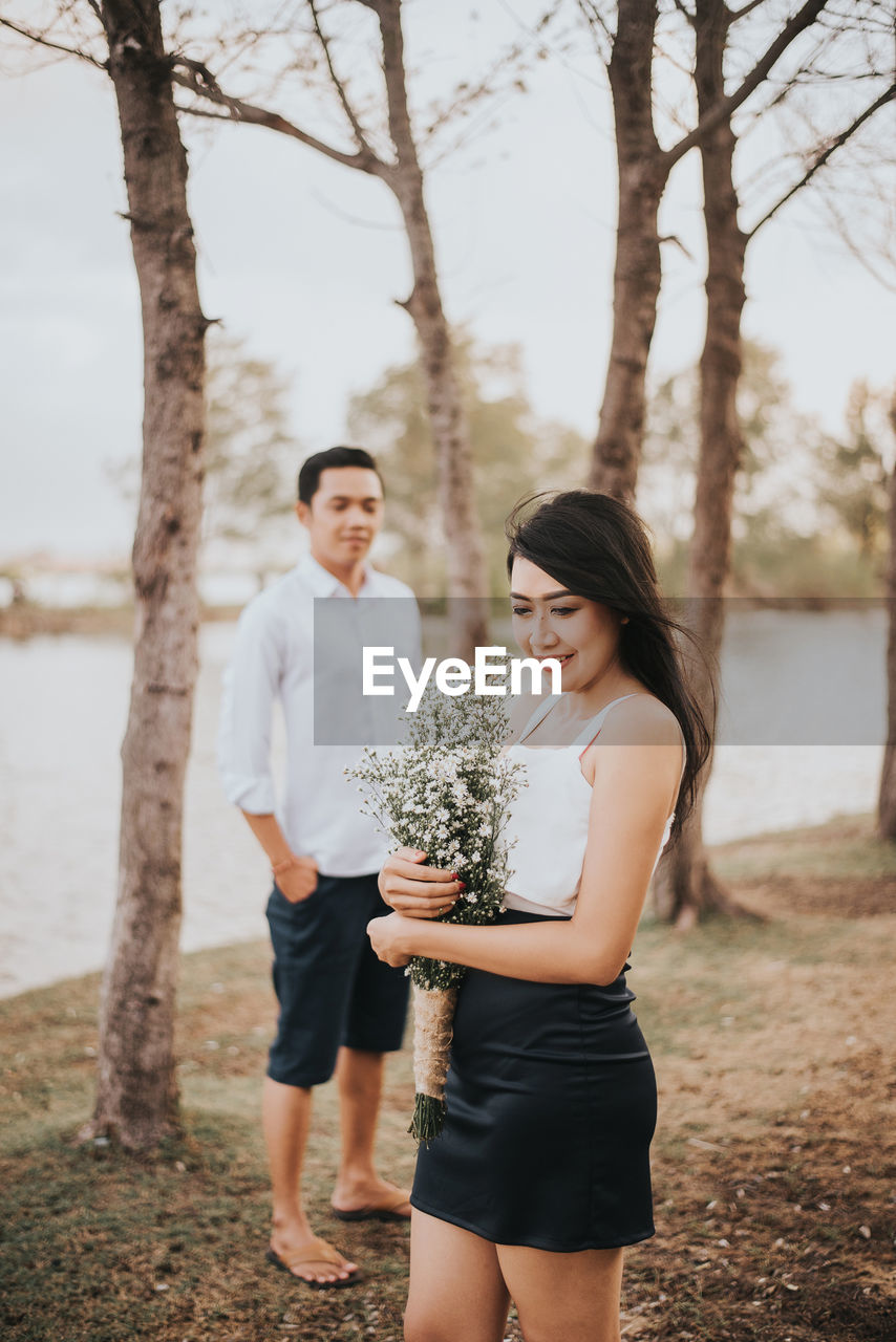 Woman Holding Bouquet While Boyfriend Standing On Land