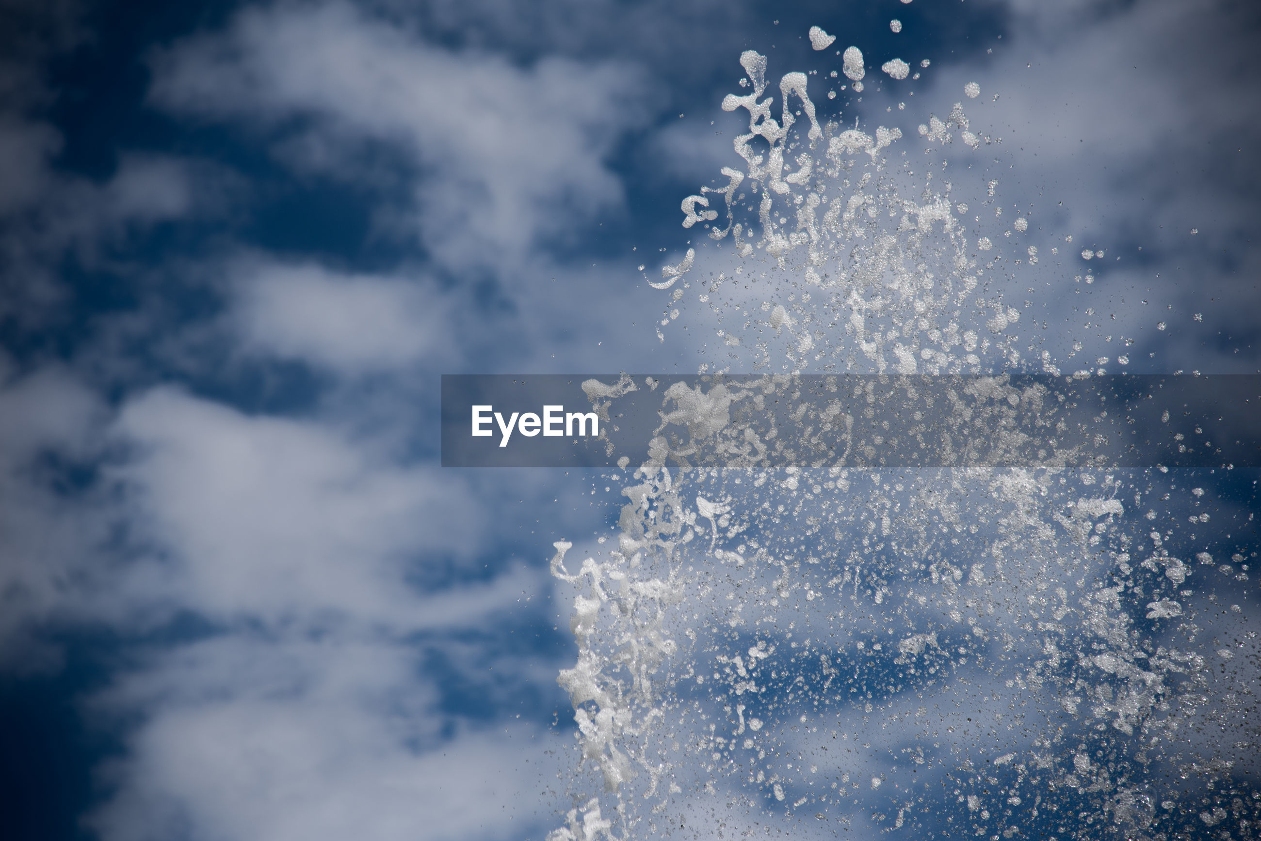 Close-up of spraying water against clouds