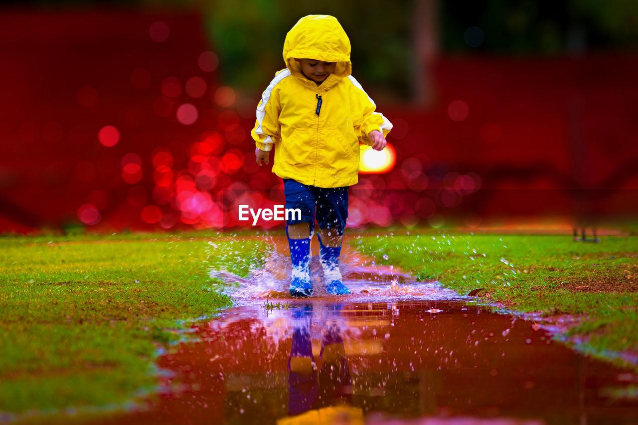 Boy wearing raincoat while splashing water in puddle