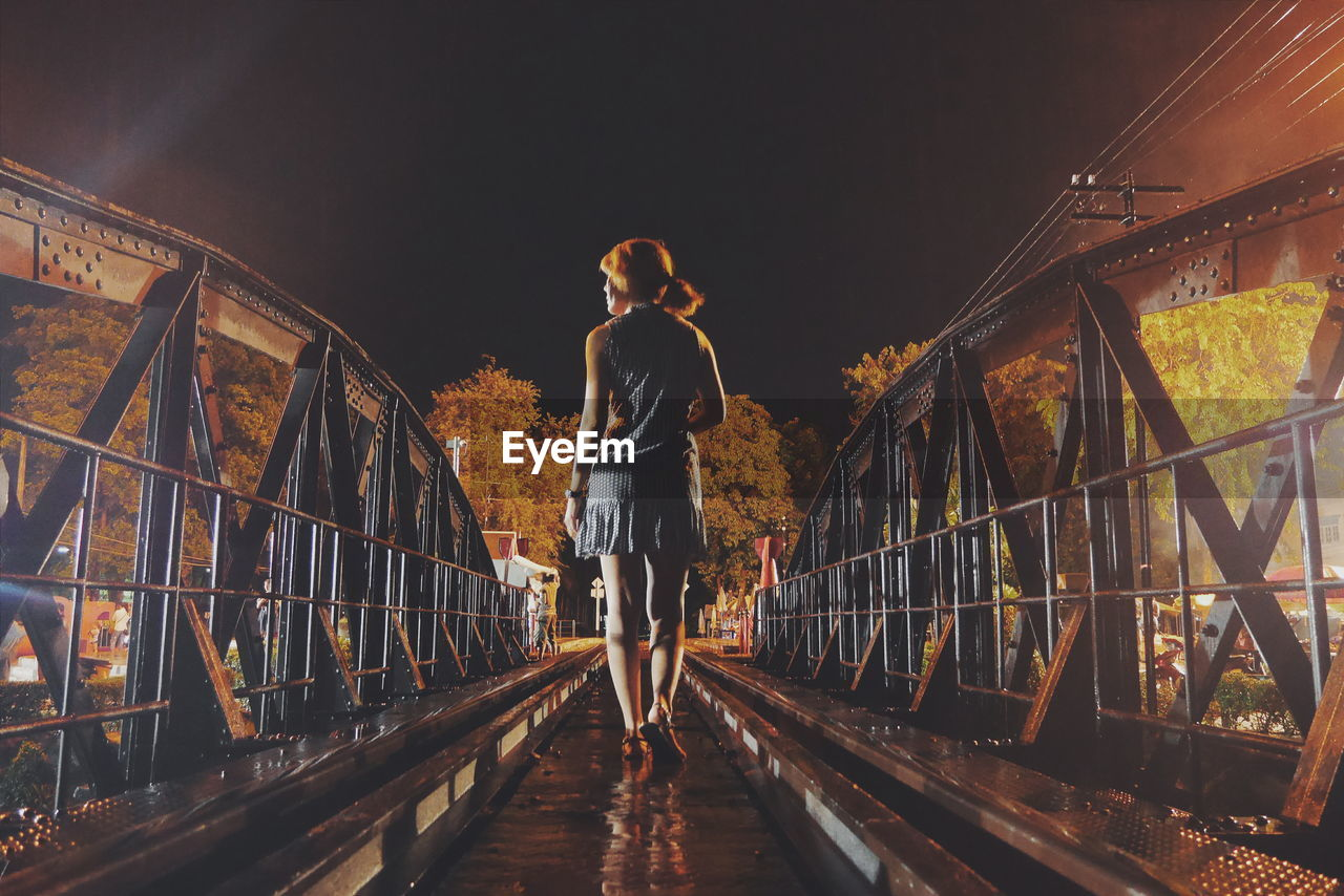 Rear view of woman walking on railway bridge at night