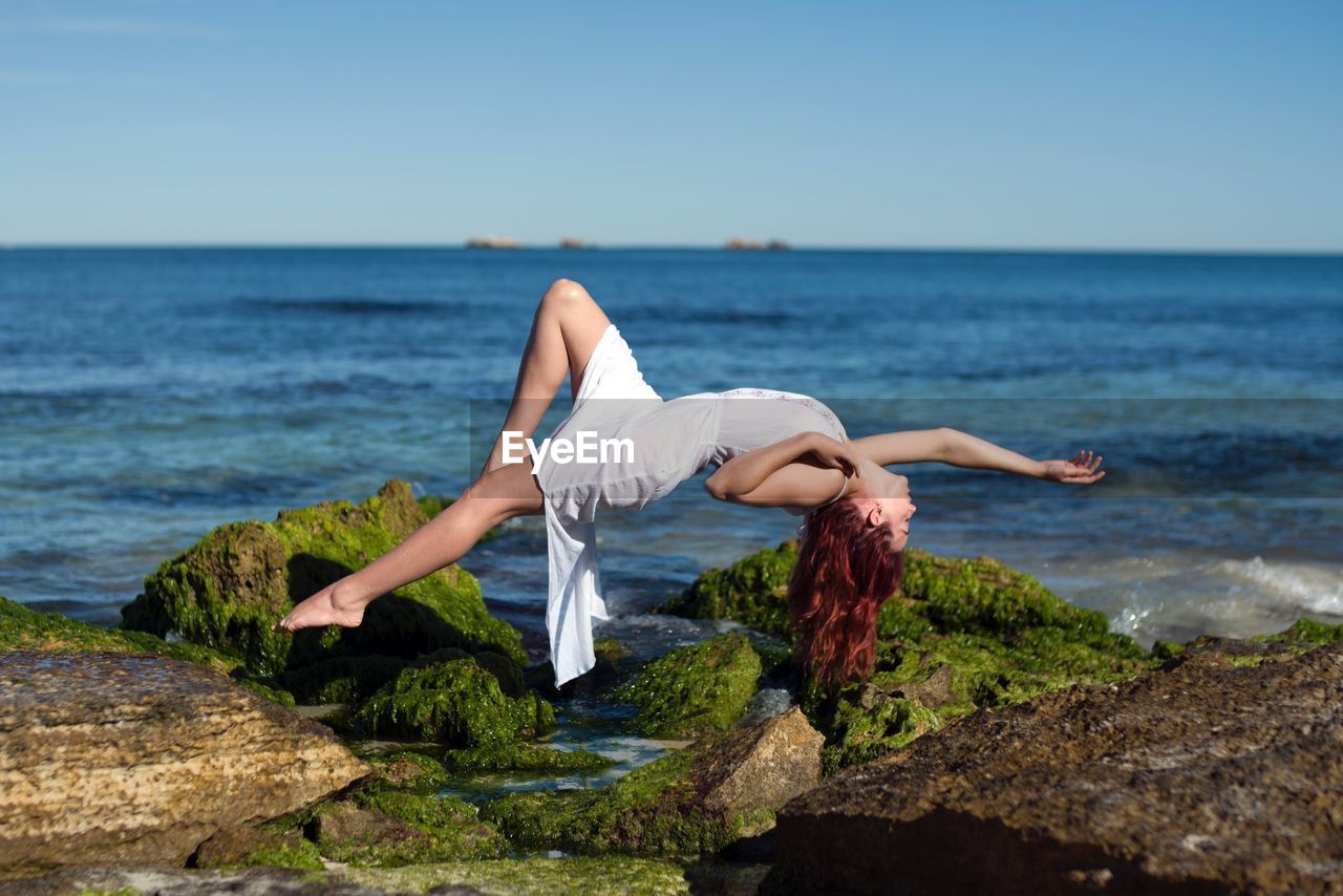 Woman levitating at beach against sky