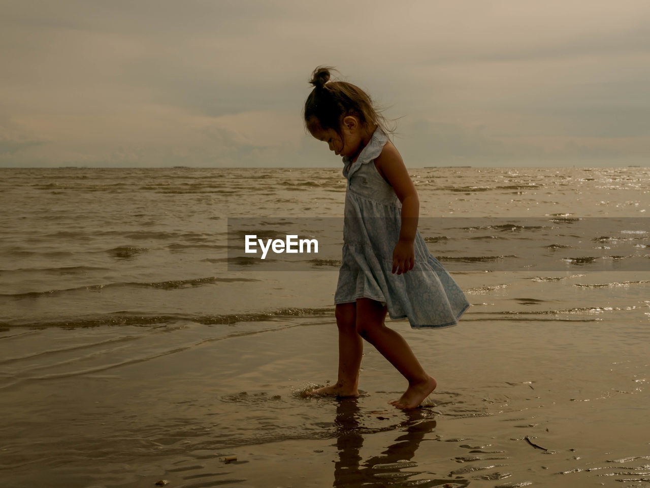 Side view of girl standing on beach against sea