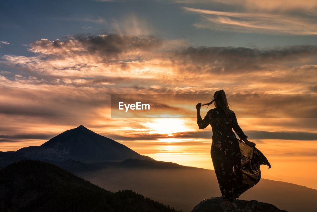 Woman Standing On Mountain Against Orange Sky