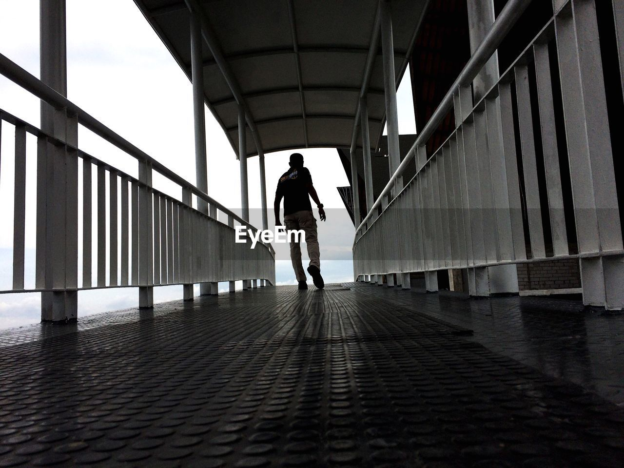 full length, one person, walking, rear view, real people, architecture, lifestyles, day, the way forward, built structure, bridge - man made structure, indoors, young adult, adult, people