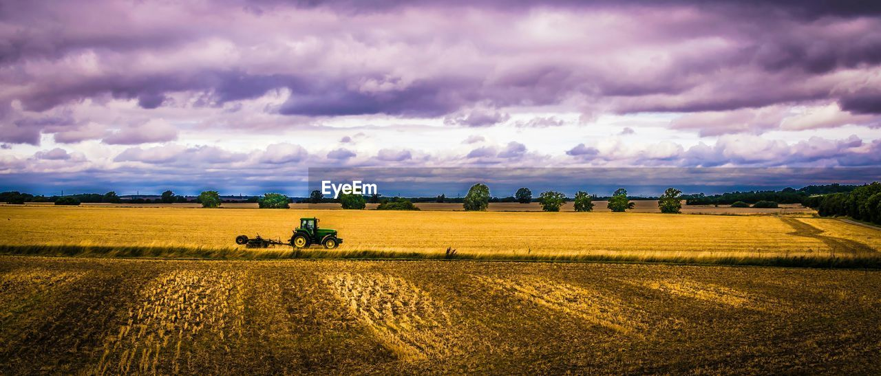 field, agriculture, landscape, cloud - sky, rural scene, sky, nature, farm, beauty in nature, scenics, agricultural machinery, tranquility, outdoors, plough, growth, combine harvester, day, cereal plant, men, tree, plowed field, one person, people