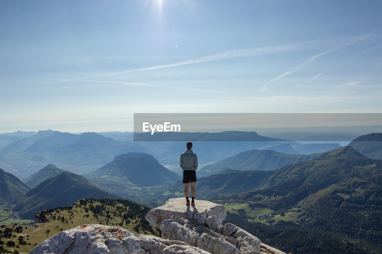 Rear view of man standing on cliff against sky