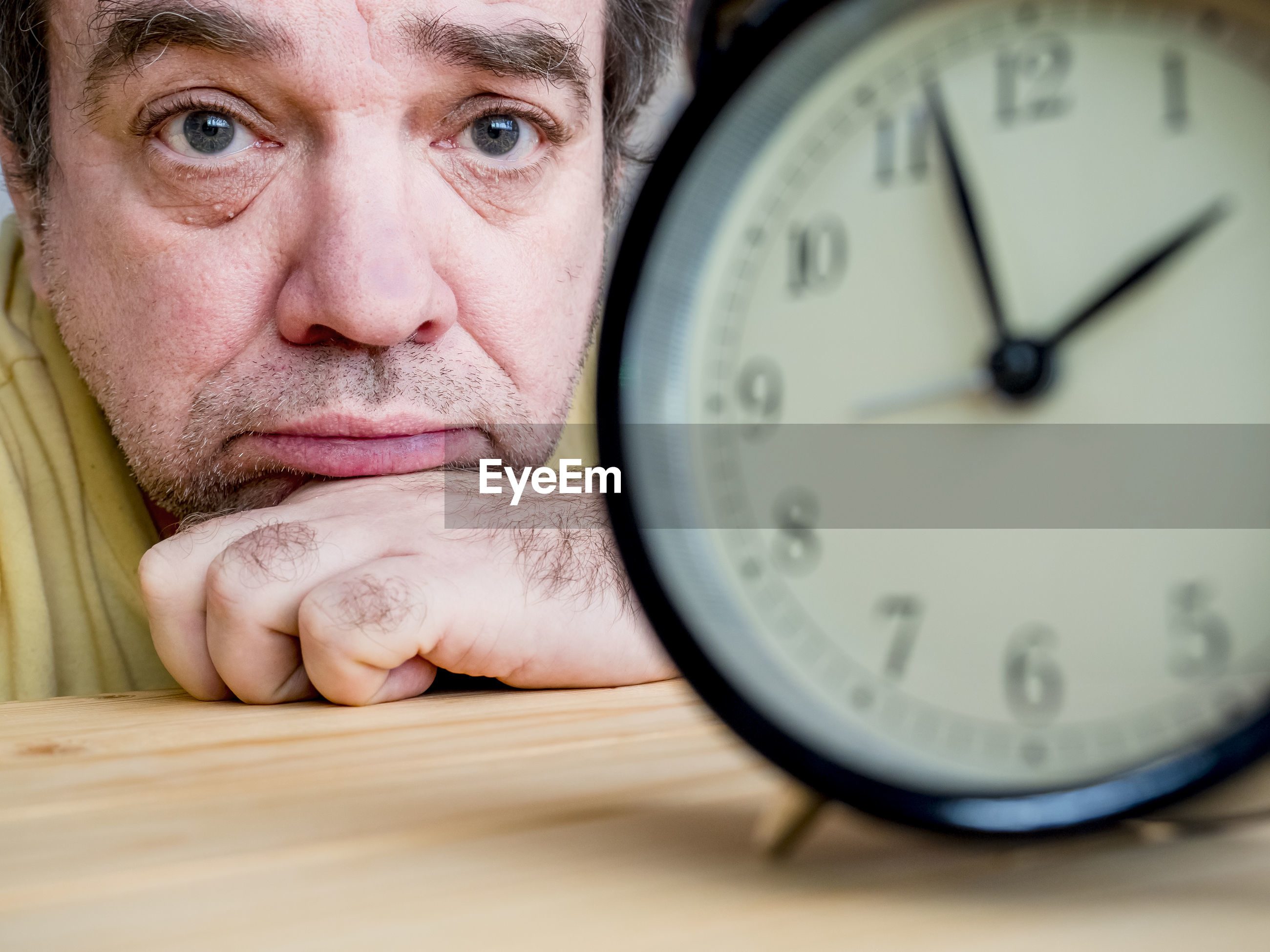 Close-up alarm clock on table with man in background