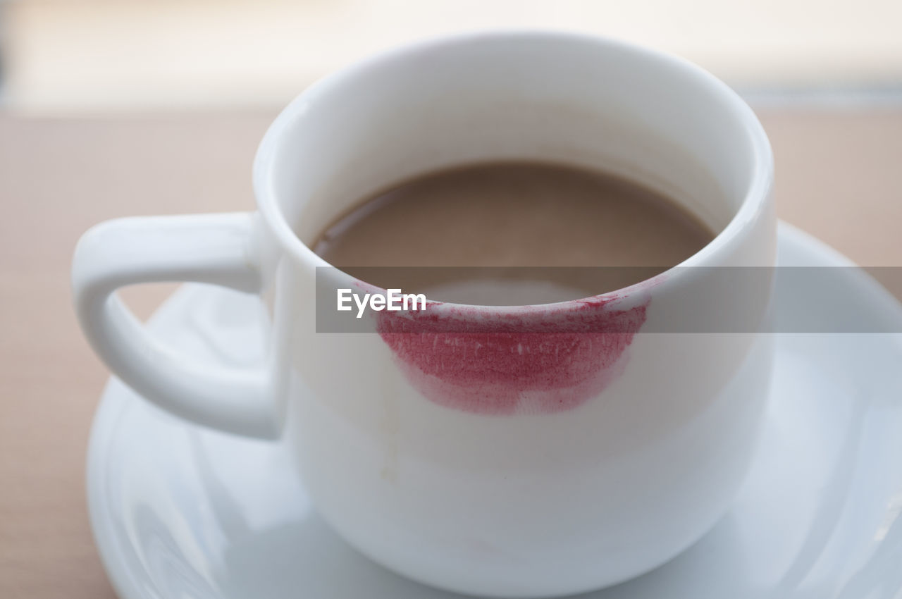 Close-up of red lipstick on coffee cup