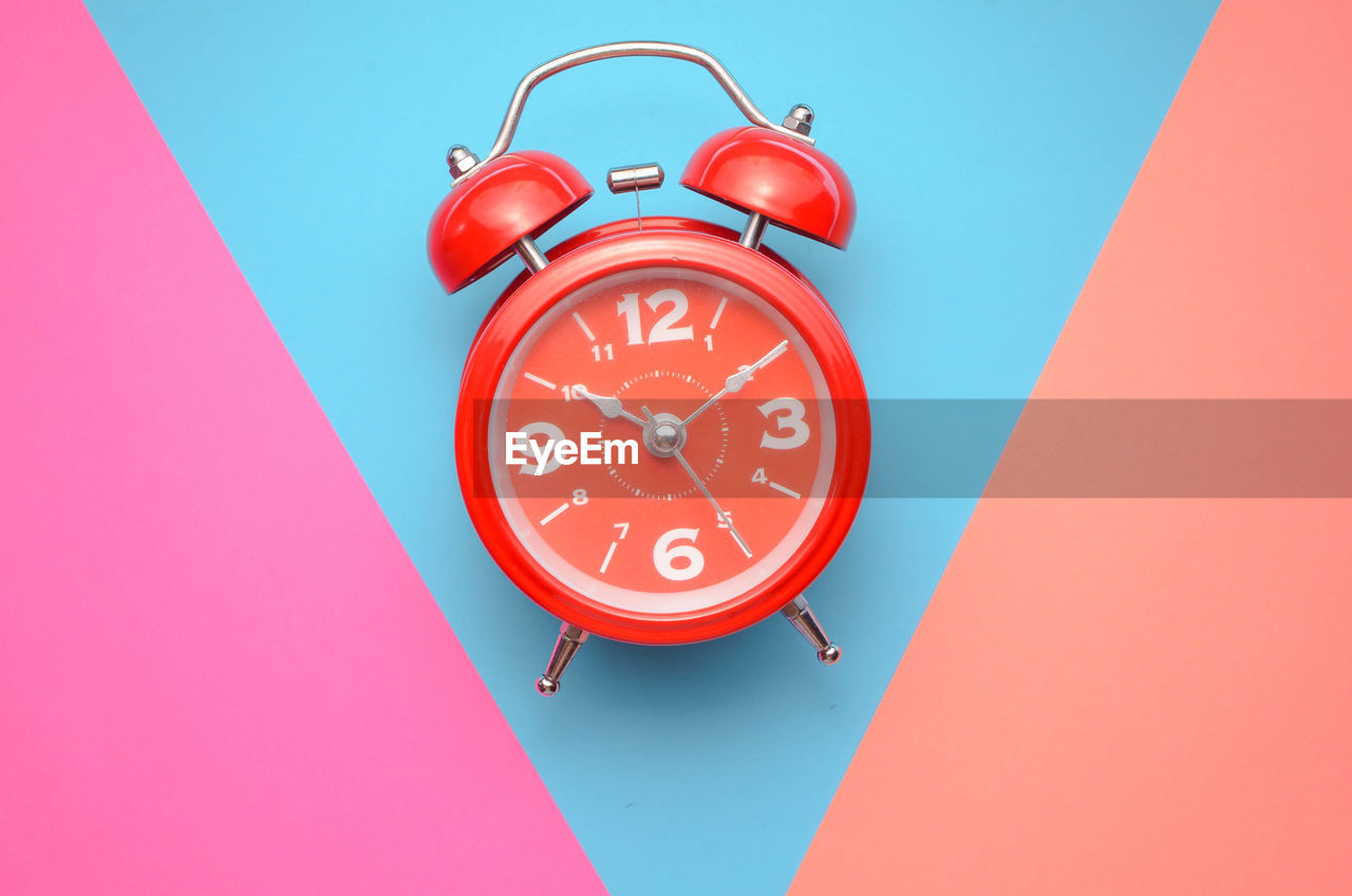 Close-Up Of Alarm Clock Over Colored Background