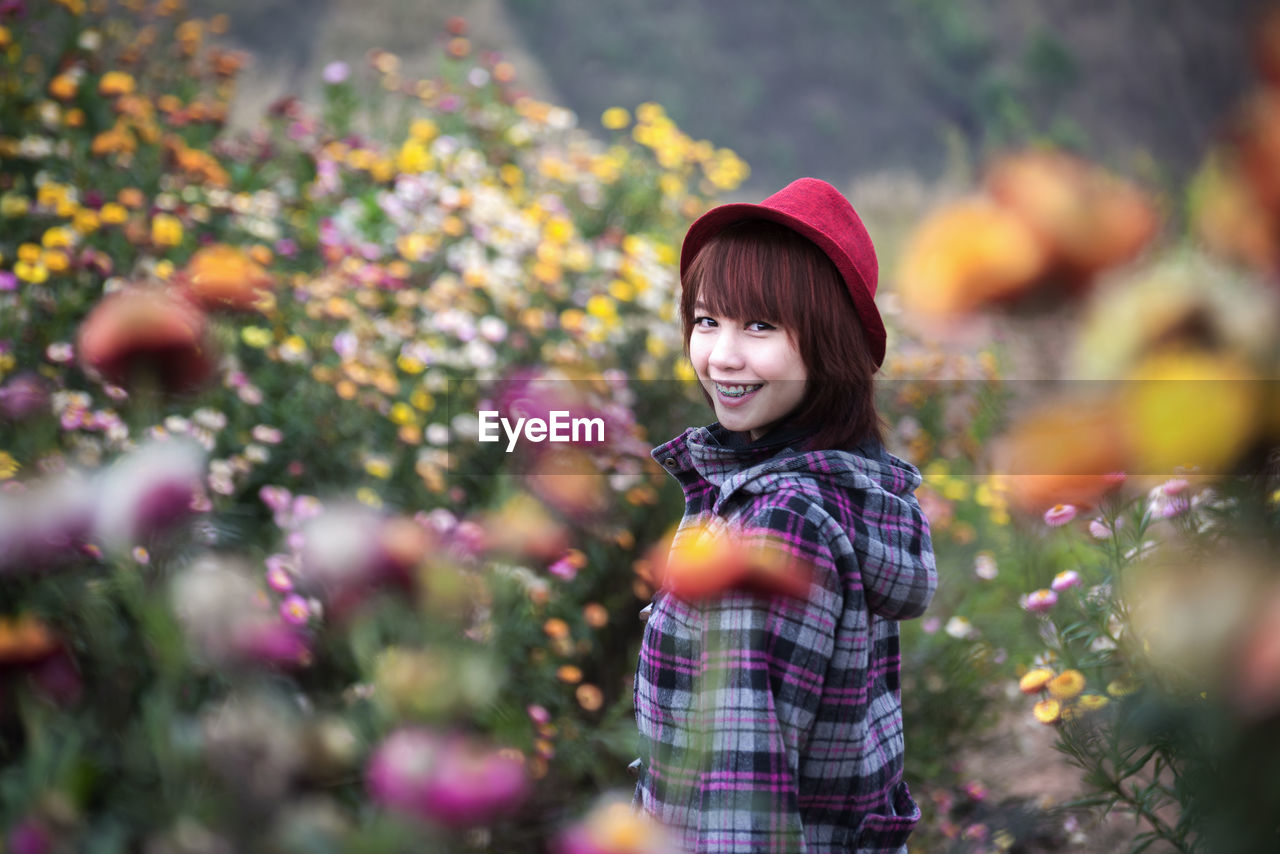 Side View Portrait Of Smiling Young Woman Standing Amidst Flowering Plants On Field