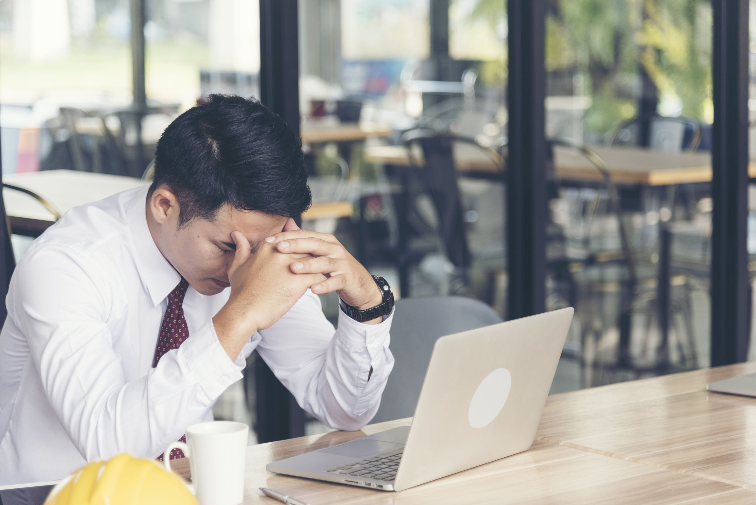 Depressed businessman sitting by table in office