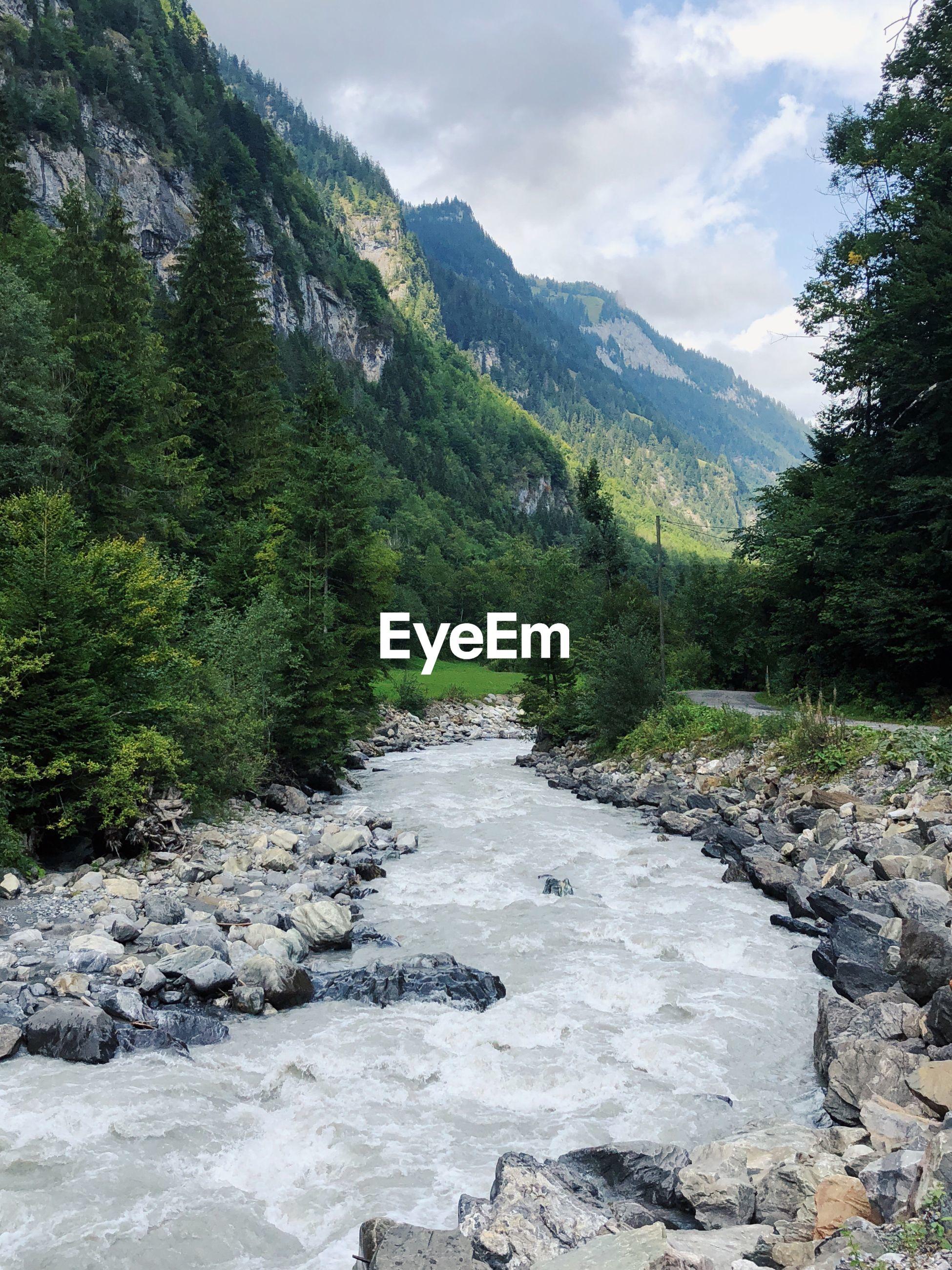STREAM FLOWING THROUGH ROCKS IN MOUNTAINS