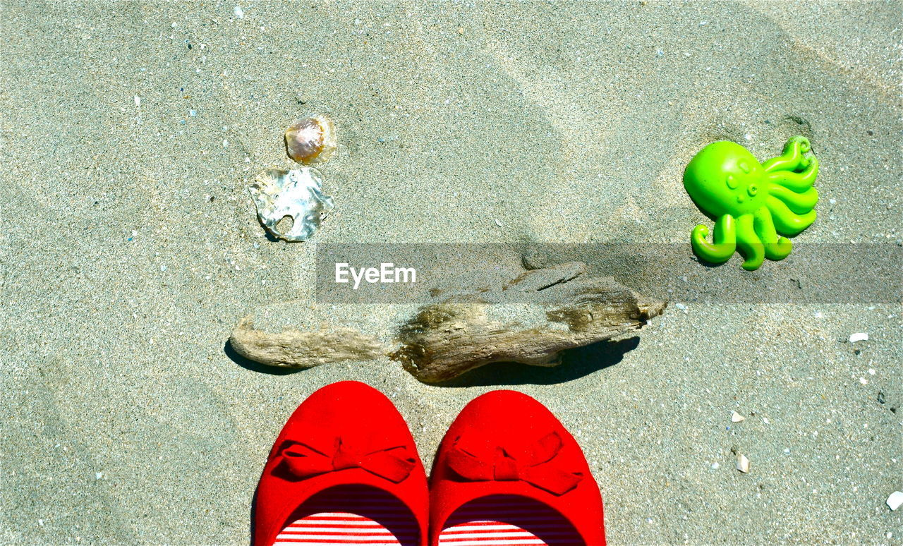 High angle view of red shoes by toys on sand at beach