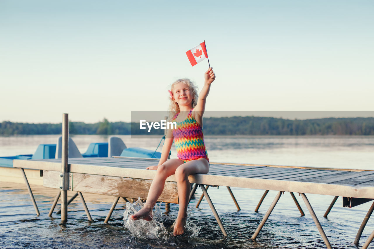 Girl sitting on dock pier by lake and waving canadian flag. canada day holiday on july outdoor.