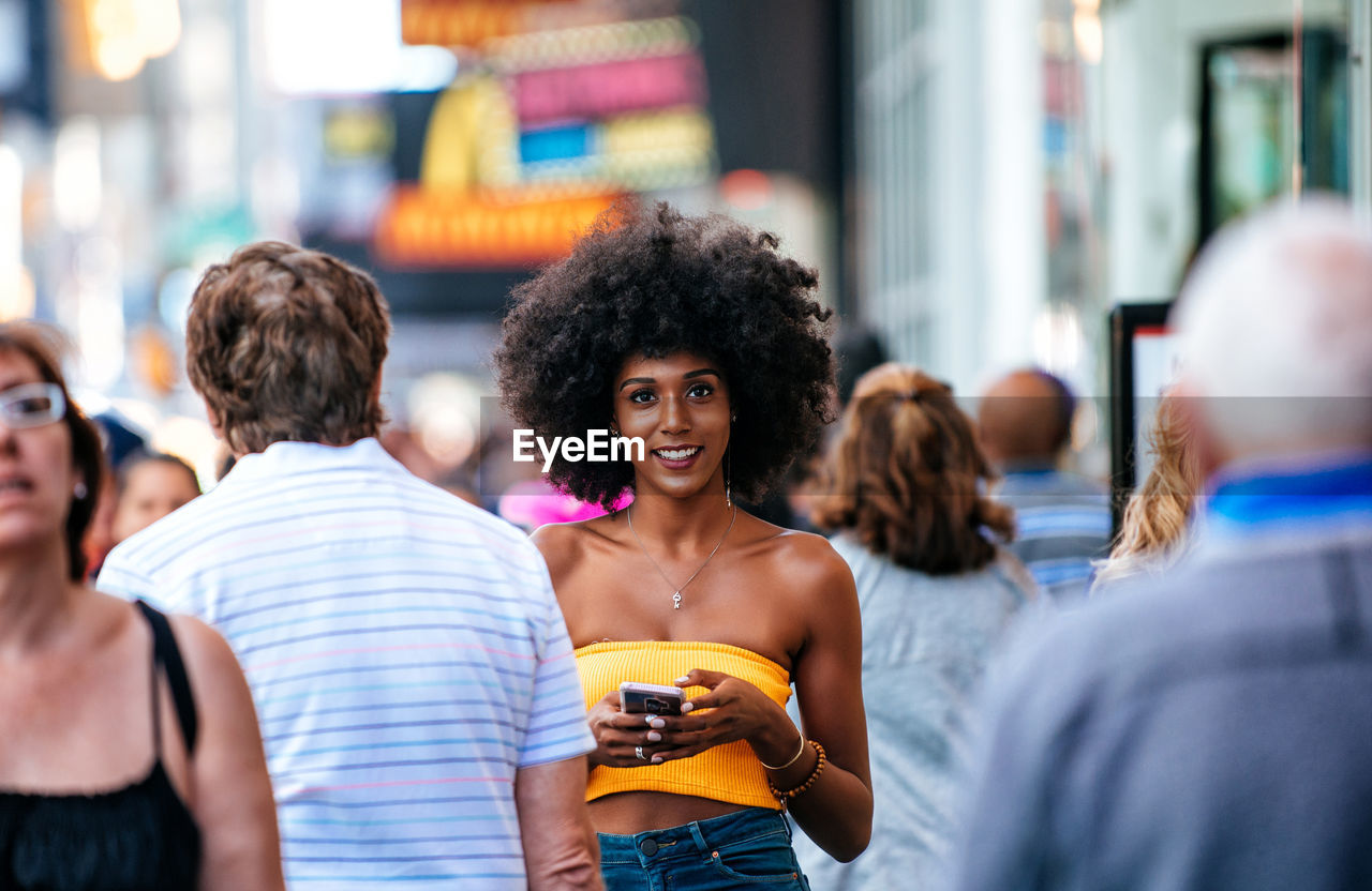 Portrait Of Happy Young Woman Holding Smart Phone On City Street