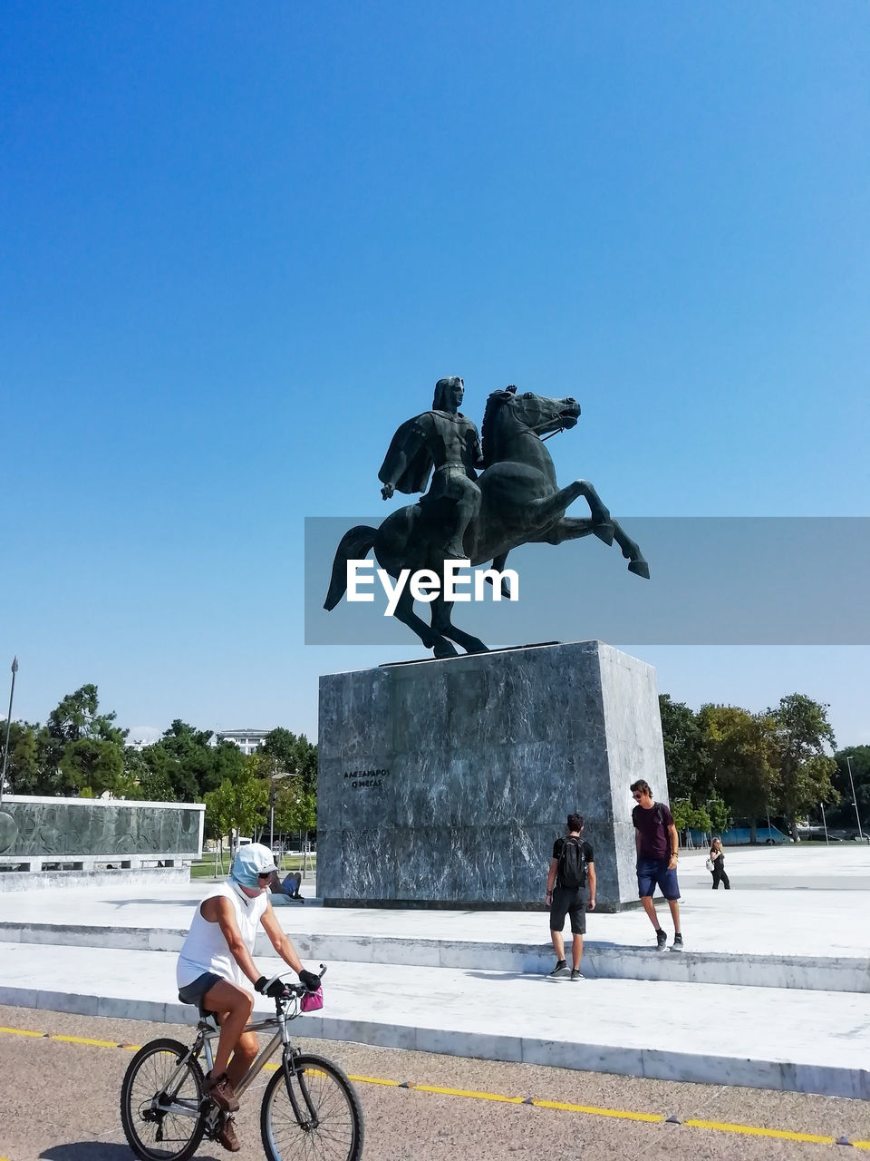 PEOPLE RIDING STATUE AGAINST CLEAR BLUE SKY