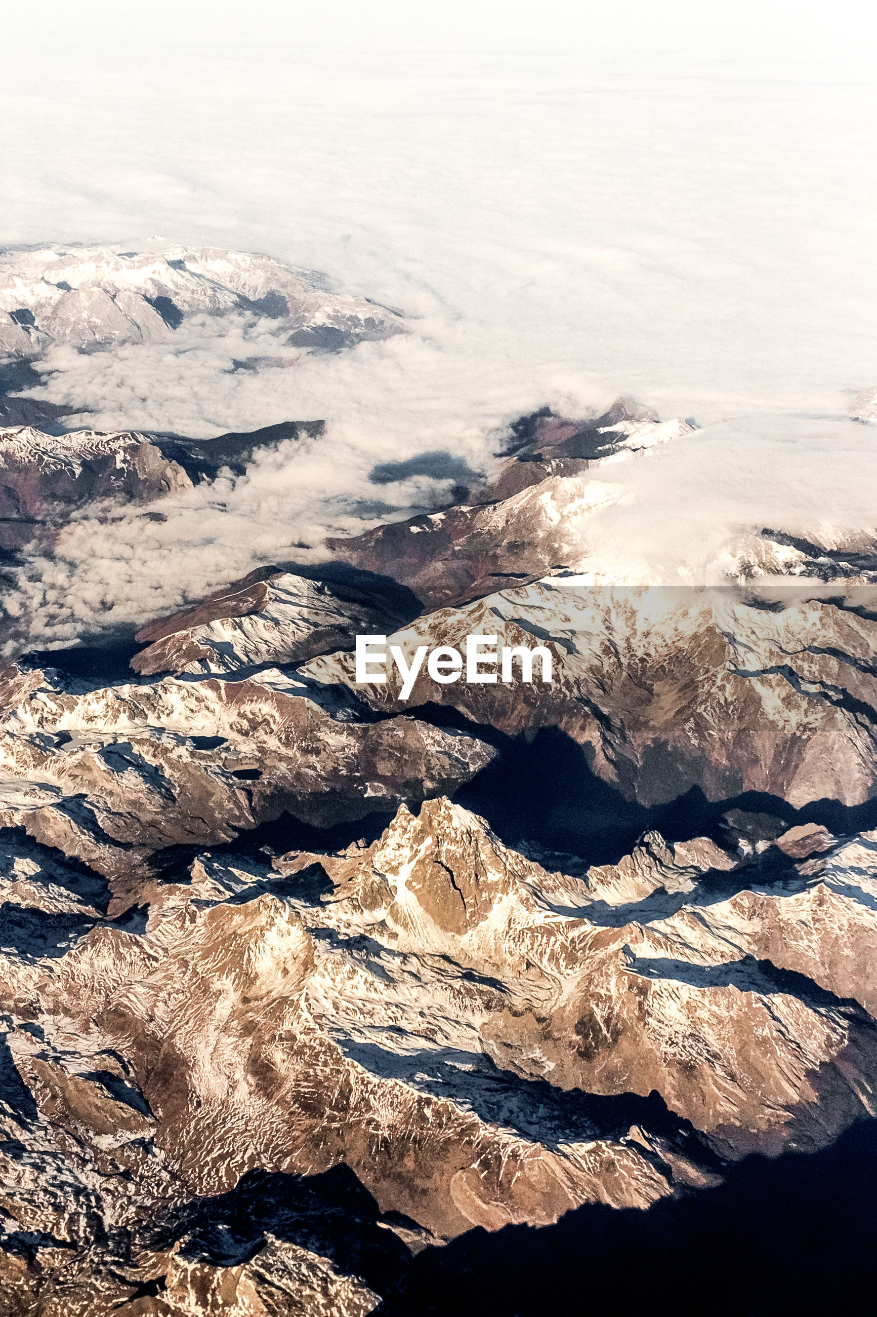 HIGH ANGLE VIEW OF SNOWCAPPED LAND AND SEA