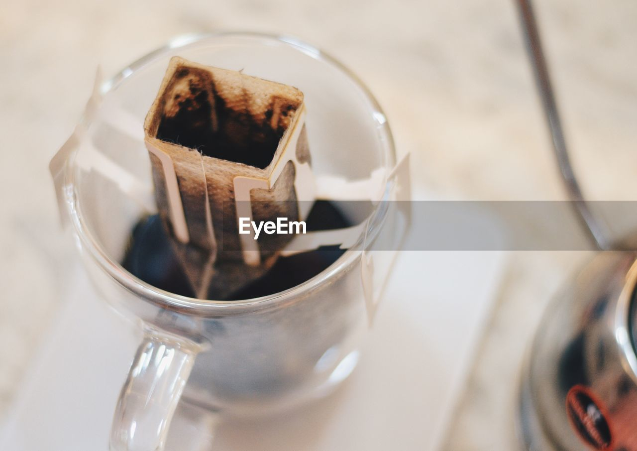 High Angle View Of Filter Over Black Coffee In Glass On Table