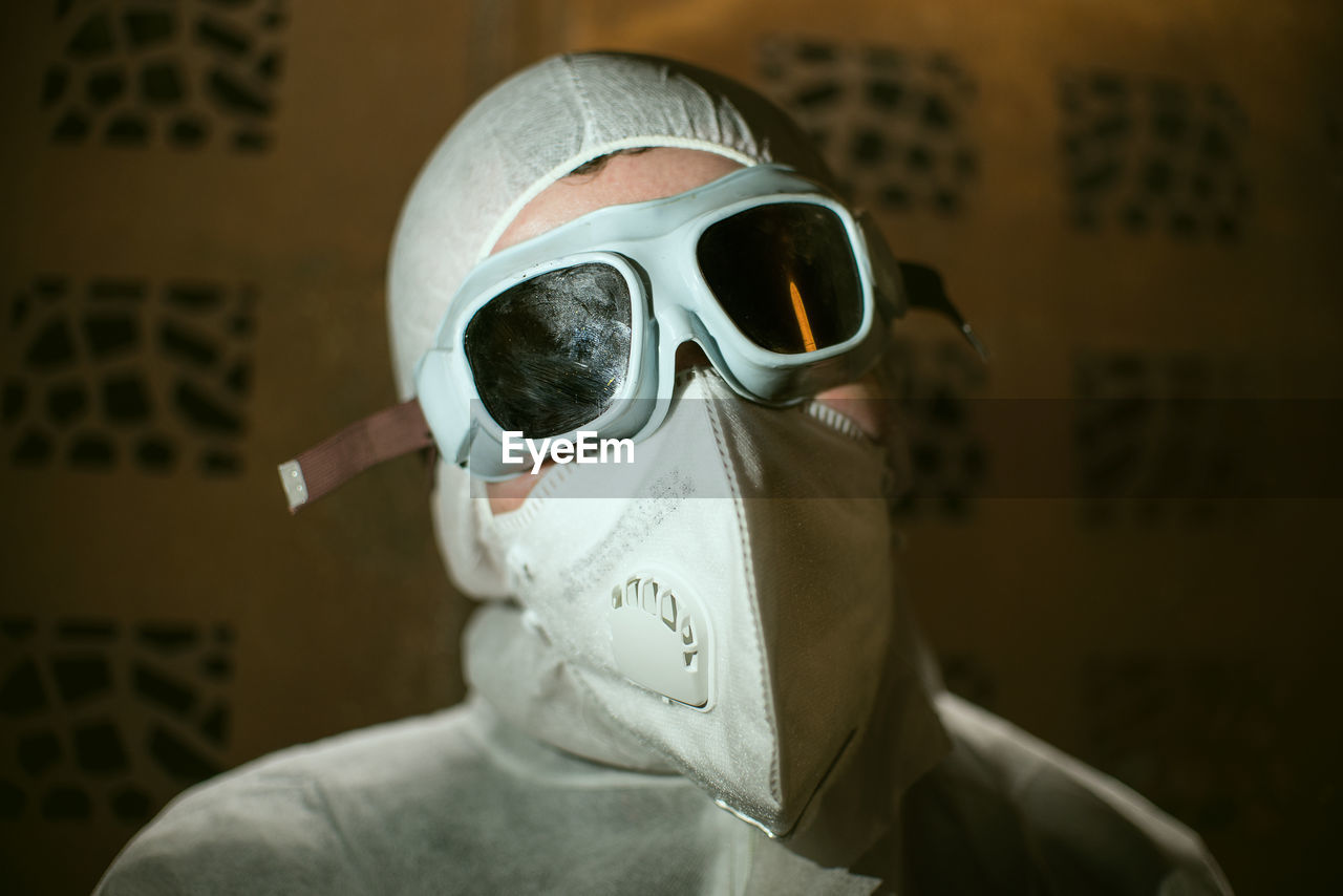 CLOSE-UP PORTRAIT OF PERSON WEARING MASK AGAINST WALL