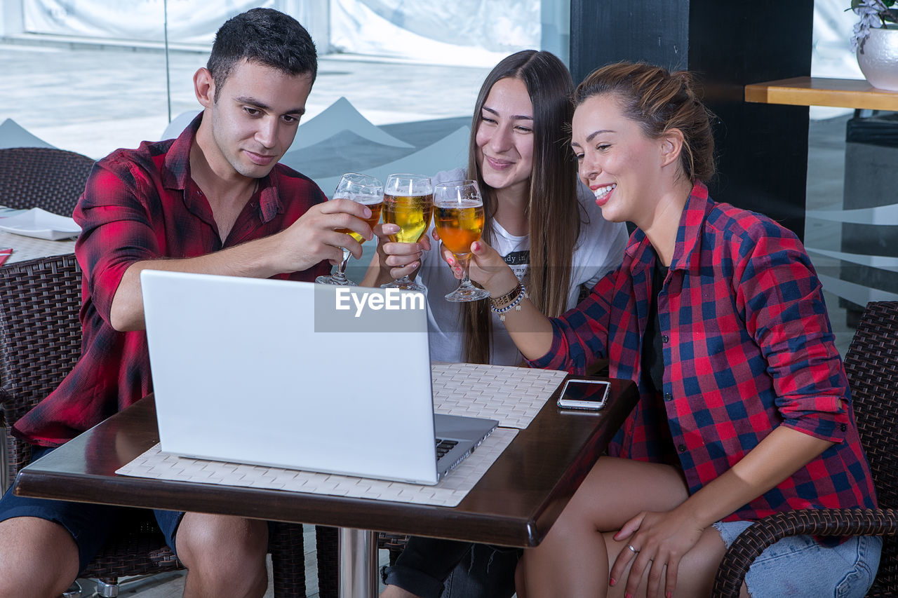 wireless technology, laptop, sitting, using laptop, smiling, communication, young adult, young women, connection, food and drink, real people, computer, technology, casual clothing, women, adult, togetherness, drink, young men
