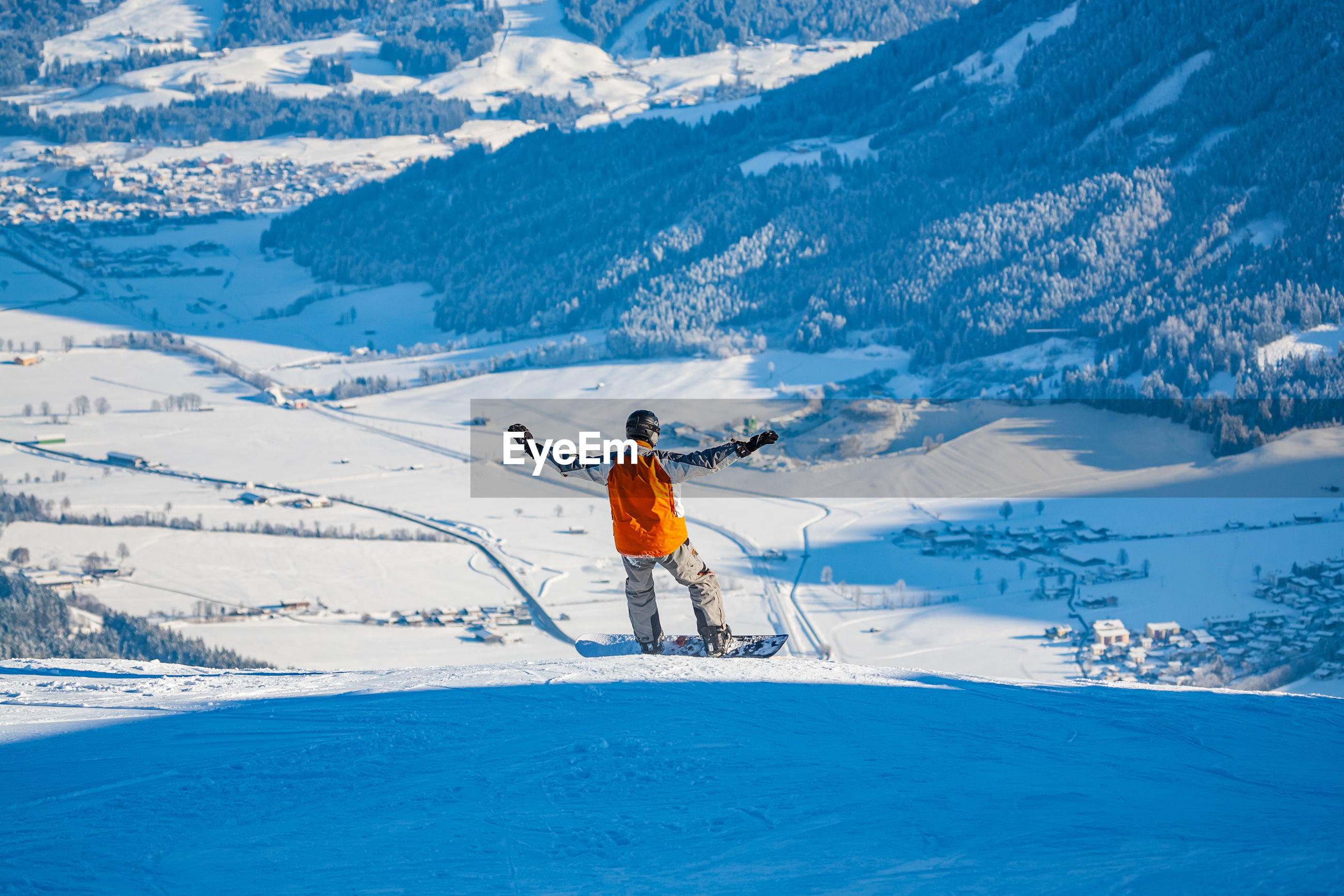 Rear view of man snowboarding on mountain
