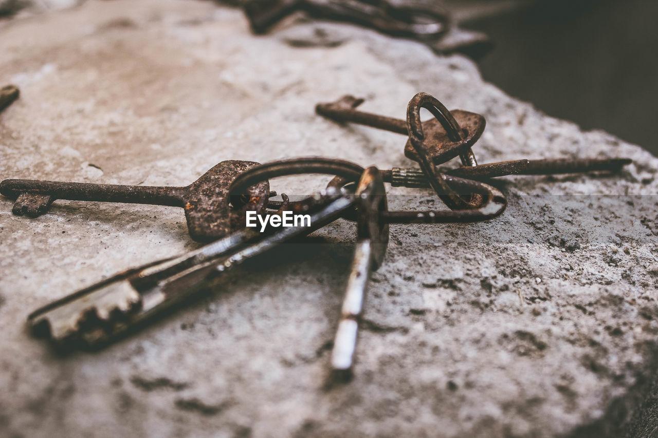 Close-up of rusty keys on rock