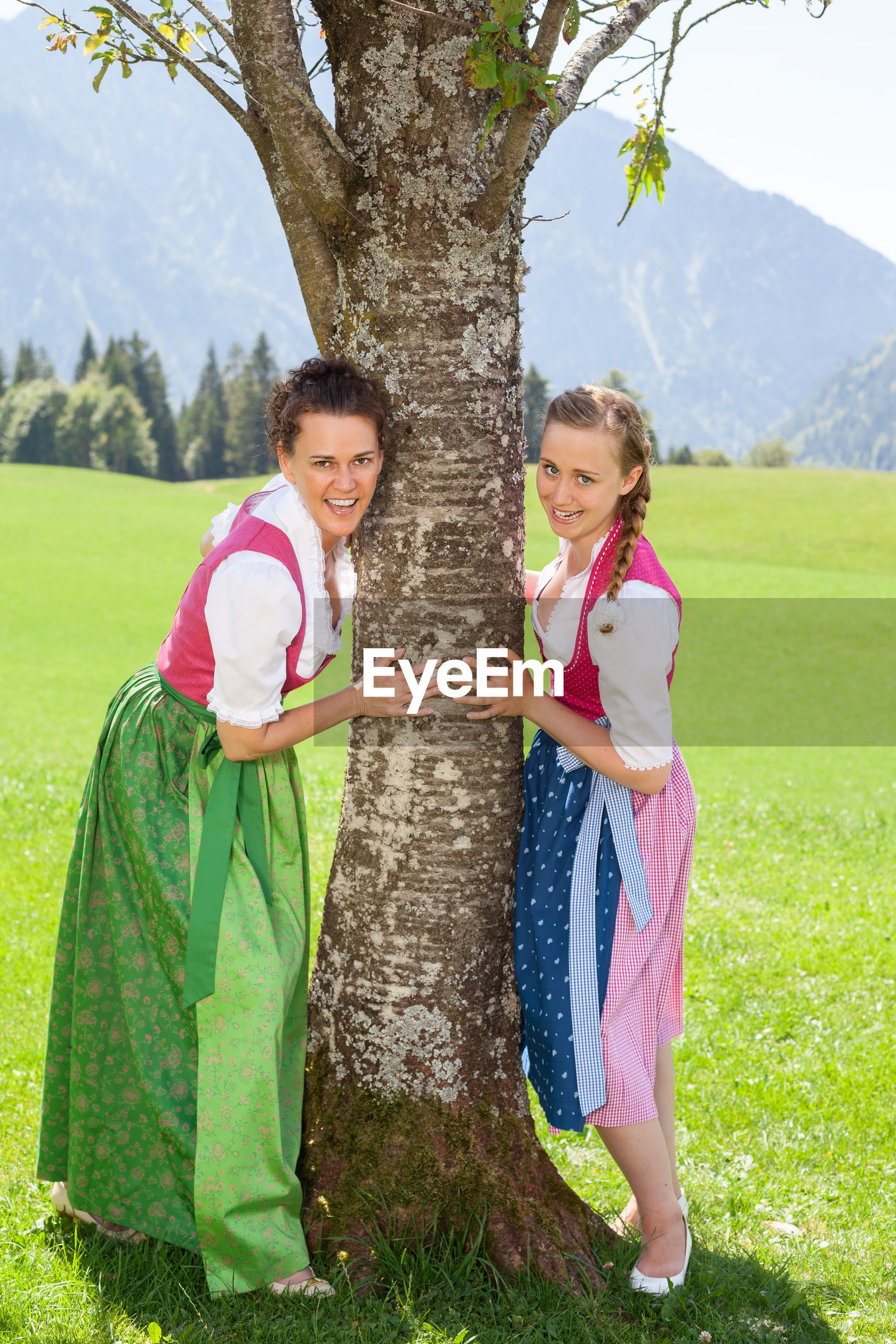 Women wearing traditional clothing while standing on grassy field