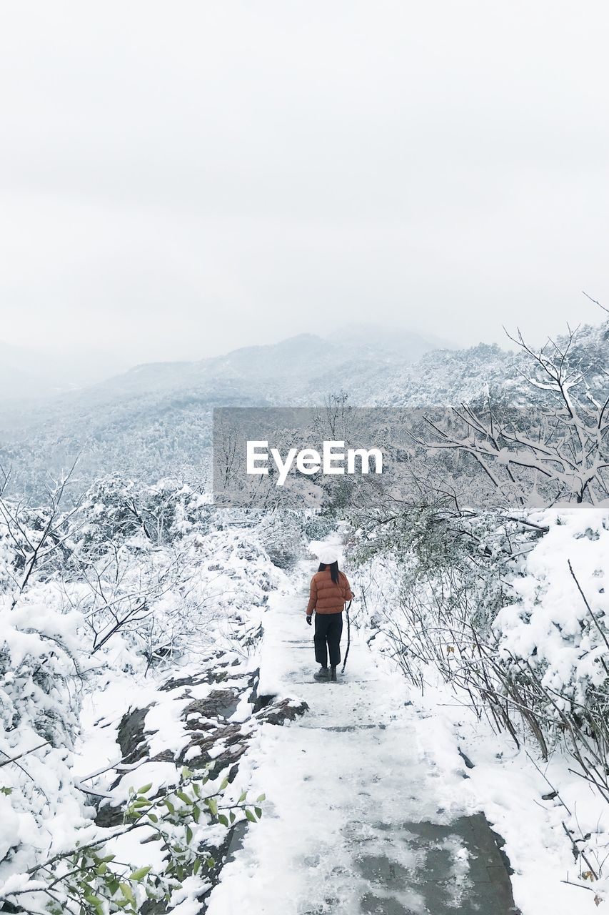 Rear View Of Woman Walking On Snow Covered Mountain Against Sky