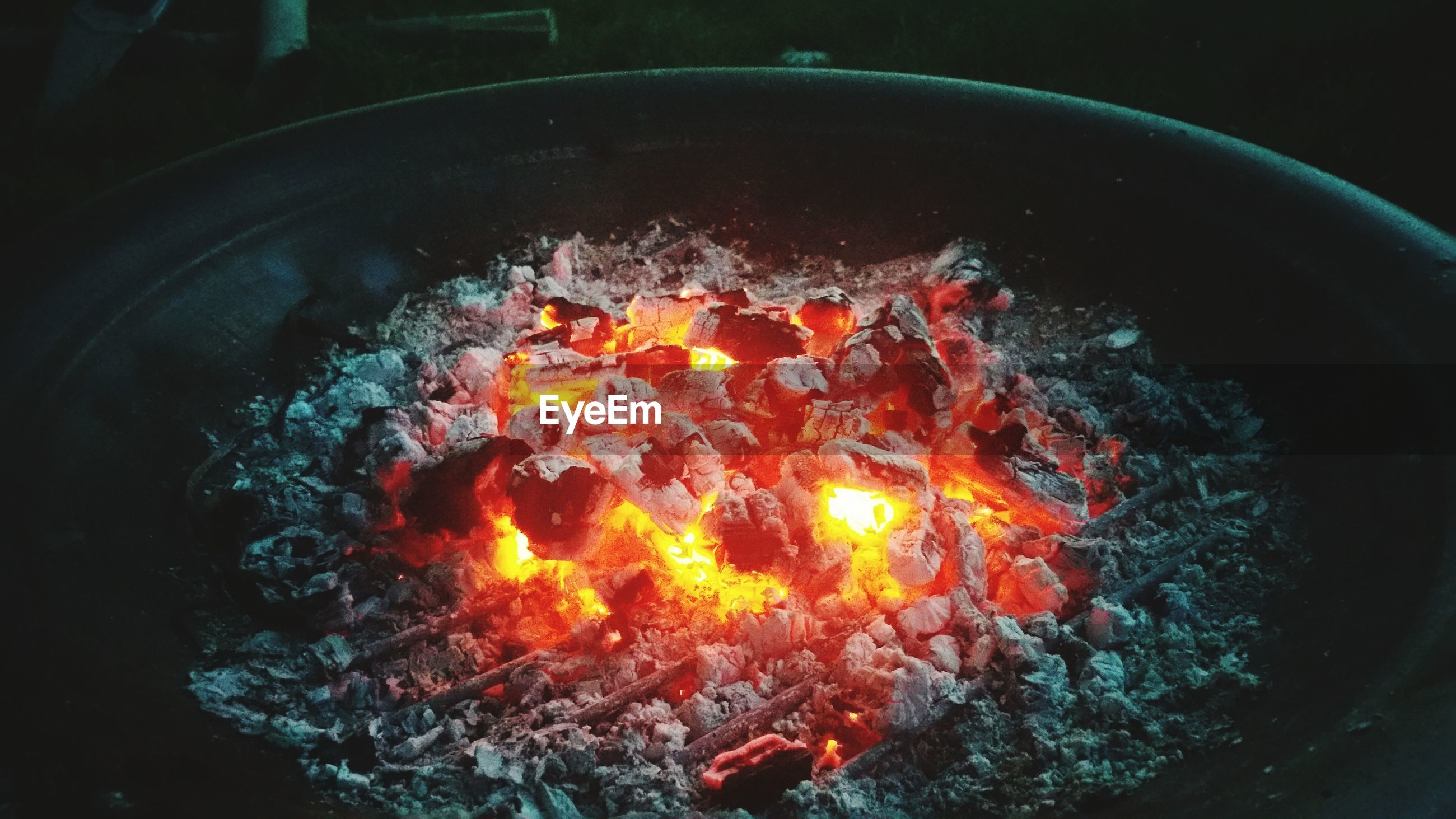 Close-up of firewood burning in container