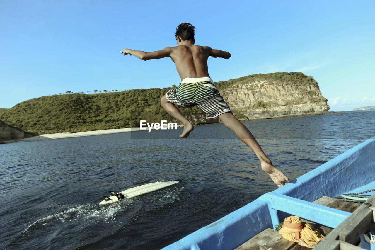 FULL LENGTH OF SHIRTLESS MAN JUMPING IN SEA