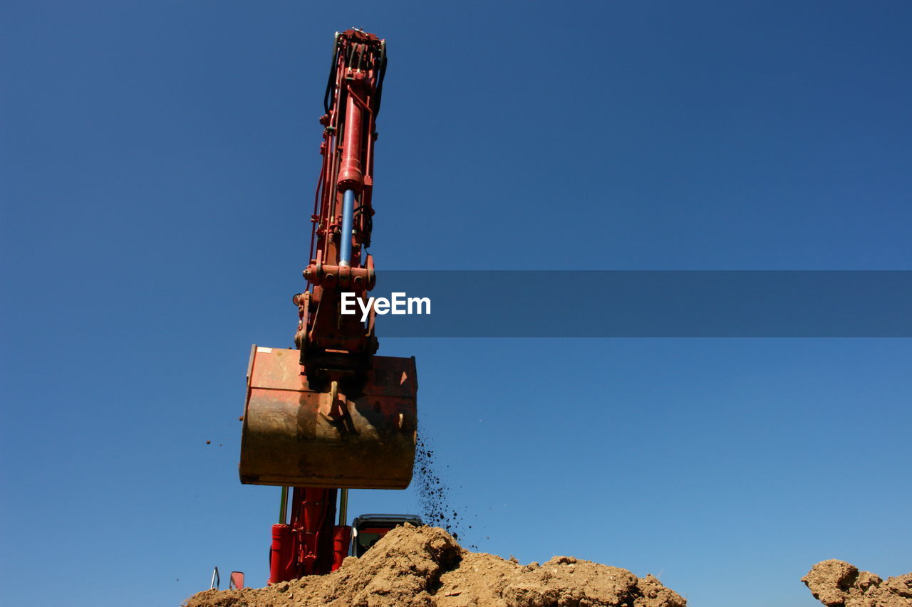 Low angle view of construction site against clear blue sky