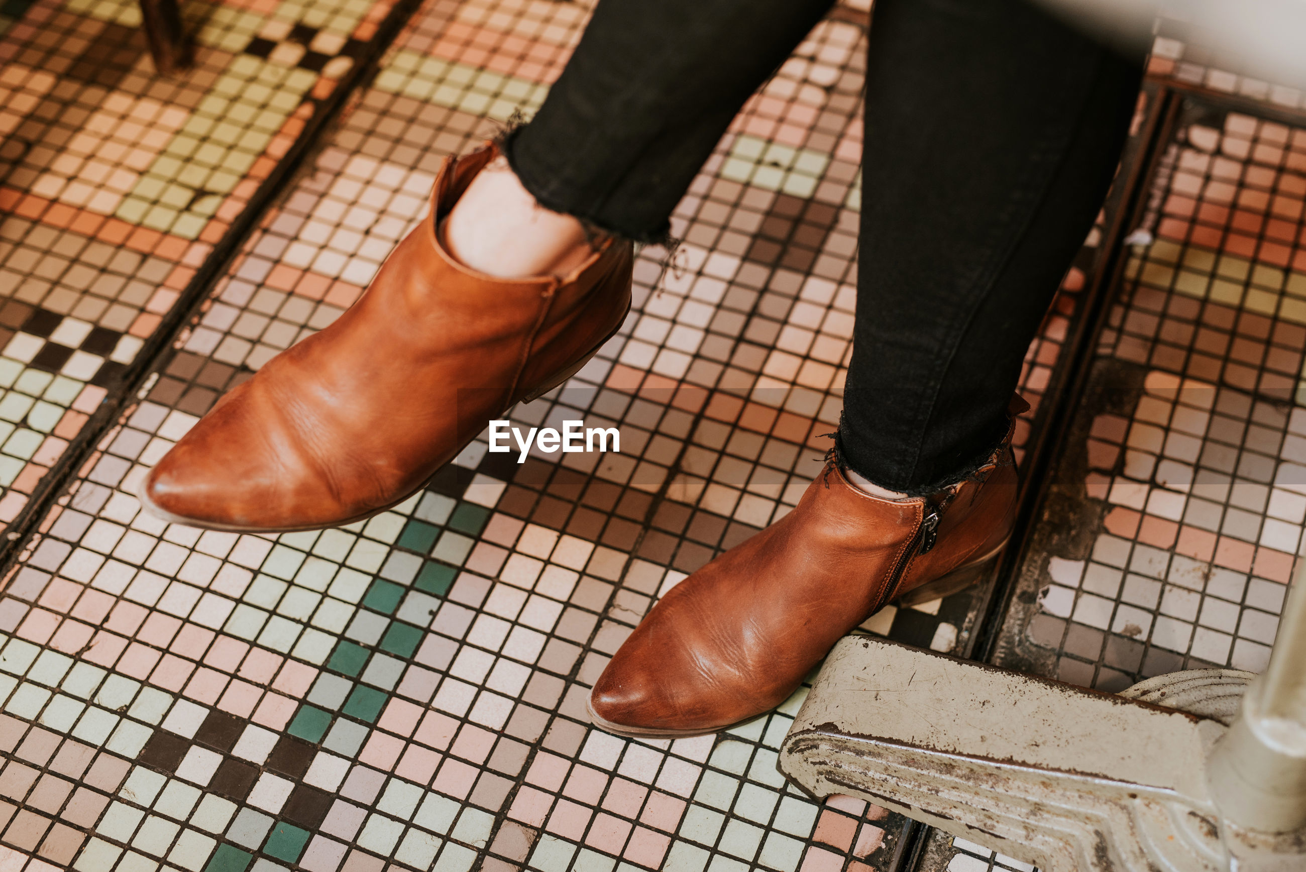 Low section of woman wearing brown shoes on tiled floor