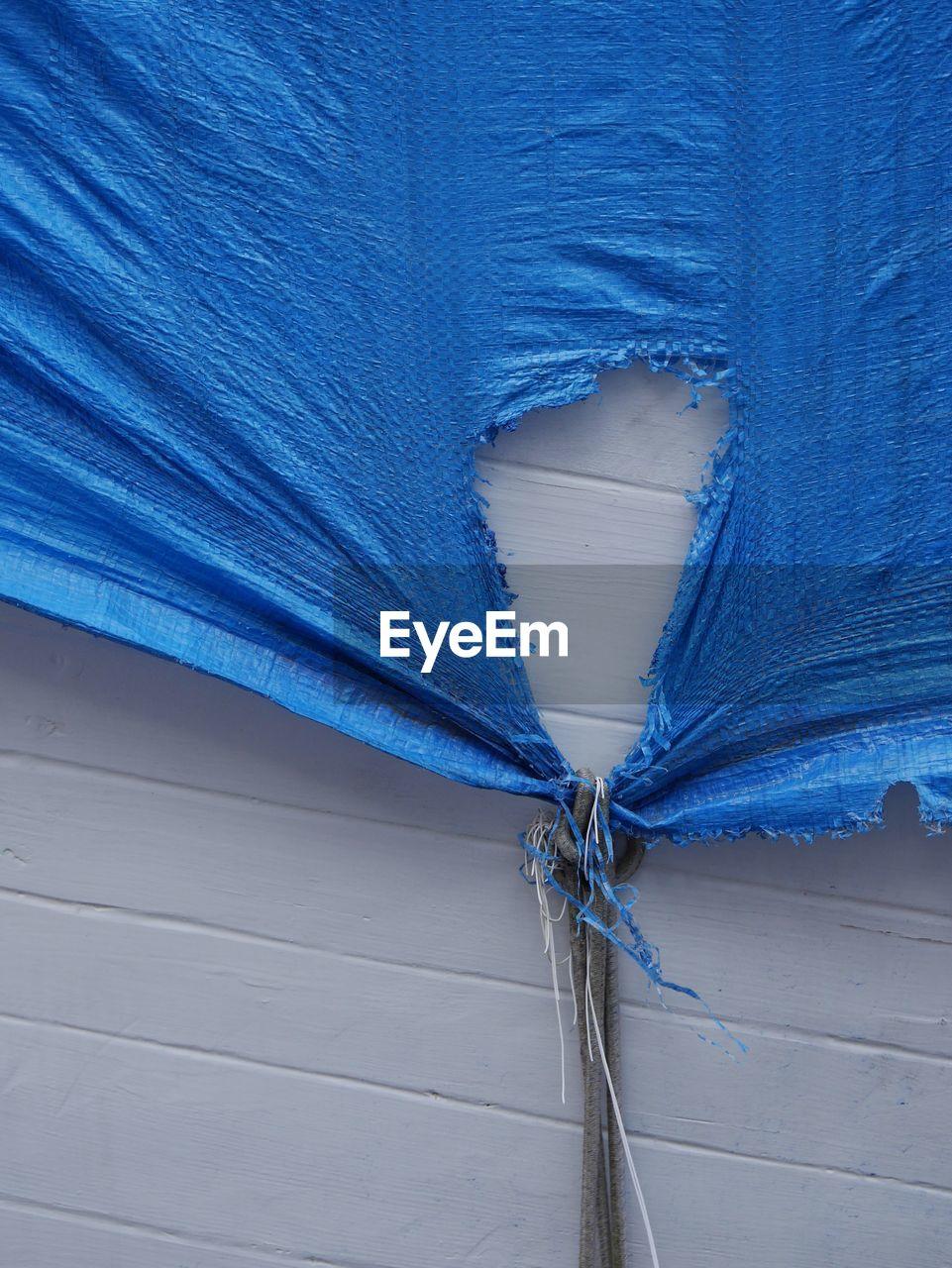 Torn blue tarpaulin on white wall