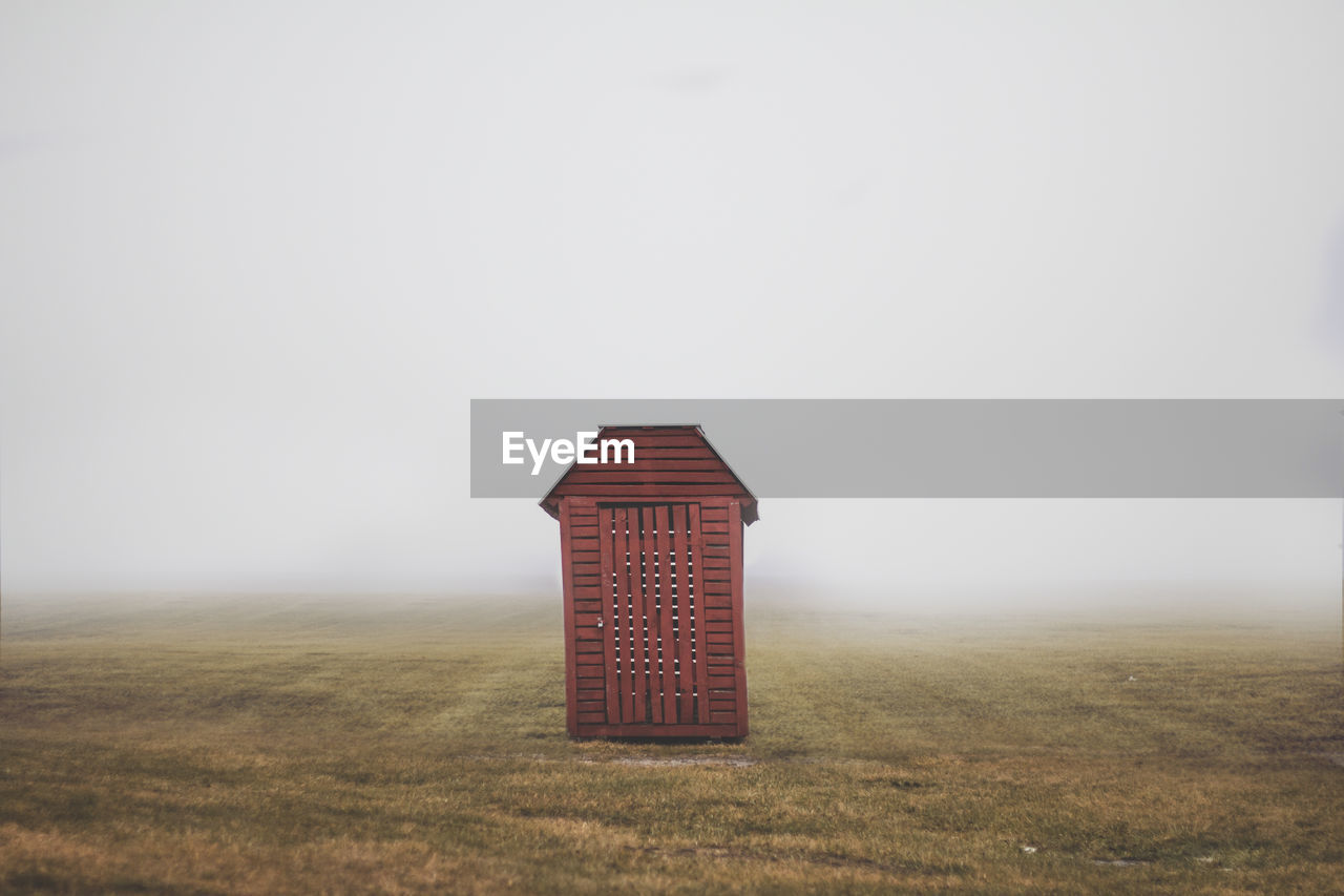 Wooden Cabin On Grassy Filed Against Sky During Foggy Weather