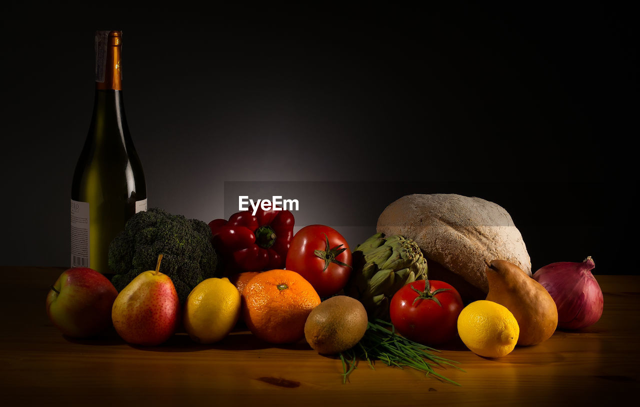 Fruits and vegetables with wine bottle on table
