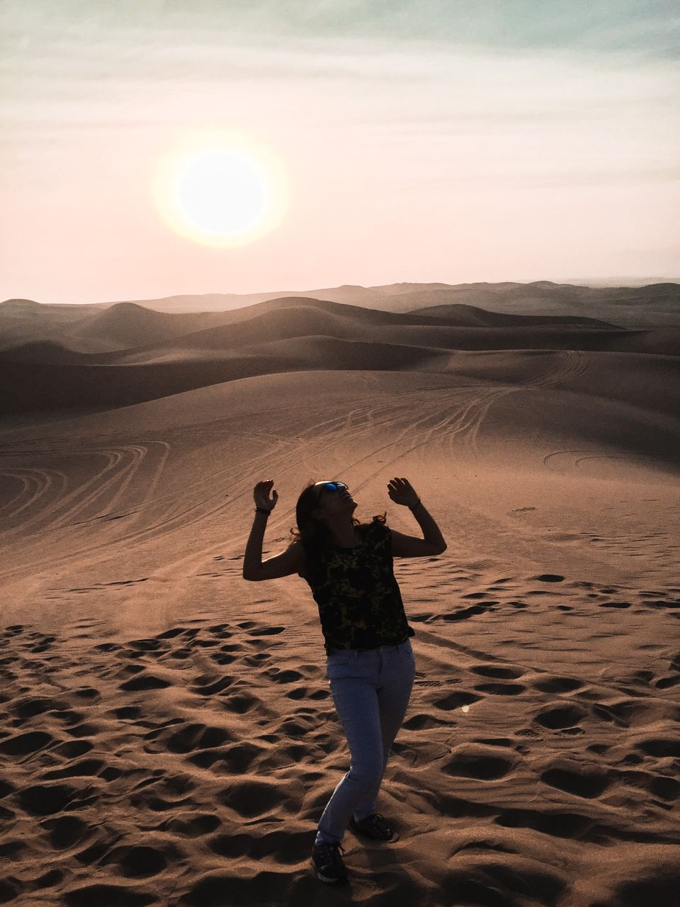 real people, beauty in nature, land, lifestyles, sky, leisure activity, one person, scenics - nature, sand, rear view, tranquility, nature, tranquil scene, sunset, sun, sunlight, full length, non-urban scene, men, arid climate, outdoors, climate, human arm