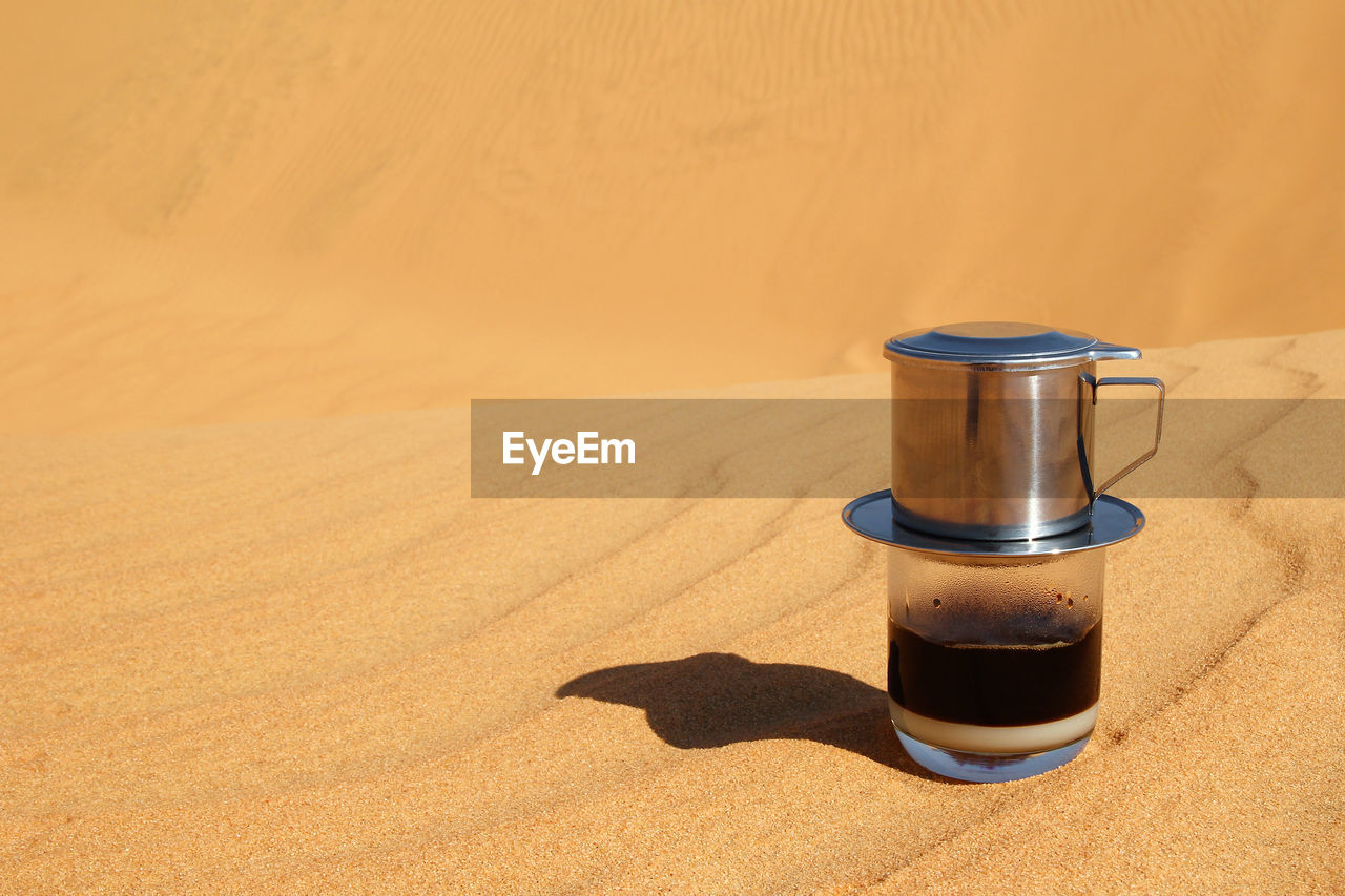 shadow, sunlight, sand, nature, no people, container, still life, sand dune, food and drink, land, table, indoors, metal, close-up, beige, drink, brown, desert, day, arid climate