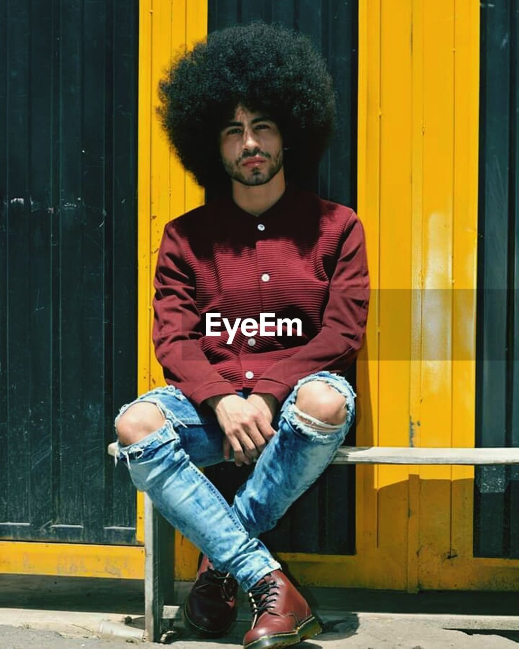 front view, one person, casual clothing, leisure activity, full length, lifestyles, real people, fashion, yellow, sitting, jeans, outdoors, curly hair, day, young adult, portrait, looking at camera, young men, building exterior
