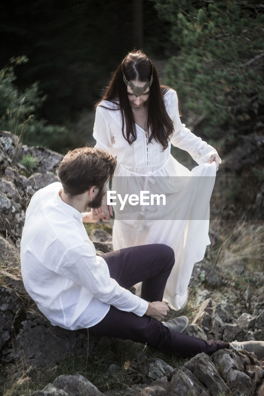 two people, real people, young adult, women, full length, adult, young women, land, lifestyles, people, casual clothing, nature, young men, togetherness, day, sitting, forest, white color, couple - relationship, hairstyle, outdoors