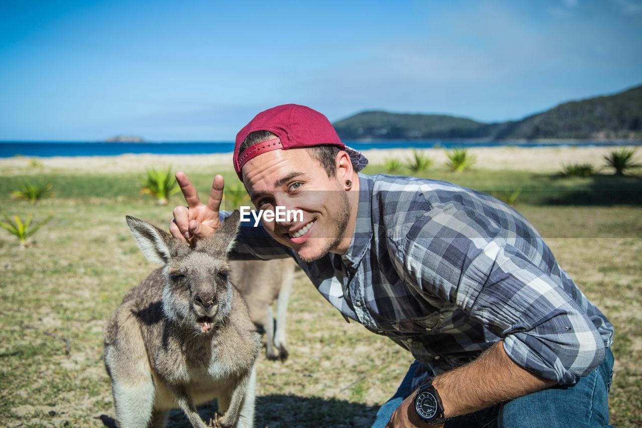 Portrait of man posing with kangaroo