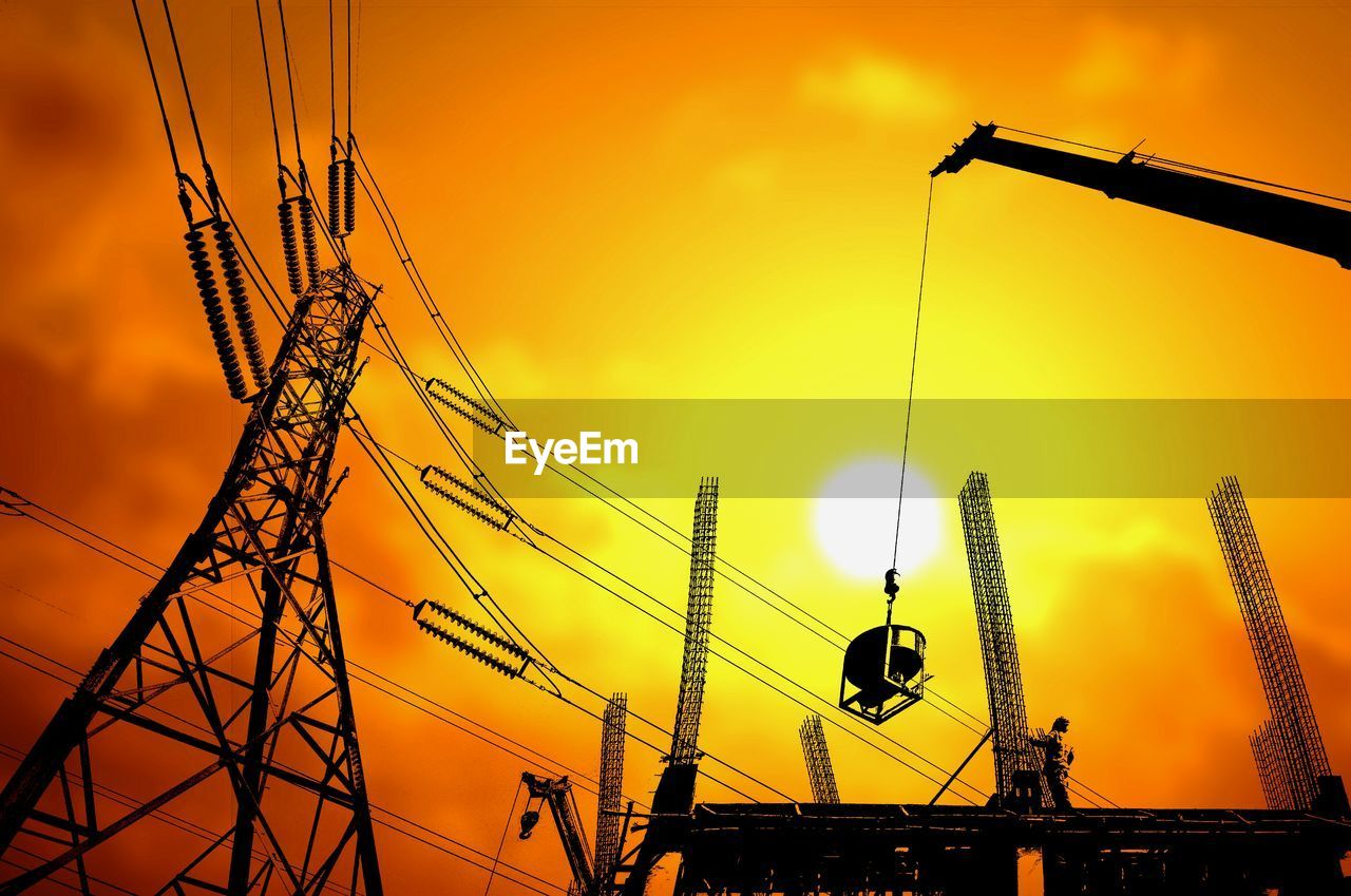 sky, sunset, low angle view, architecture, built structure, orange color, nature, no people, silhouette, connection, cable, yellow, lighting equipment, outdoors, machinery, crane - construction machinery, technology, building exterior, construction industry, power line, electricity, power supply, construction equipment