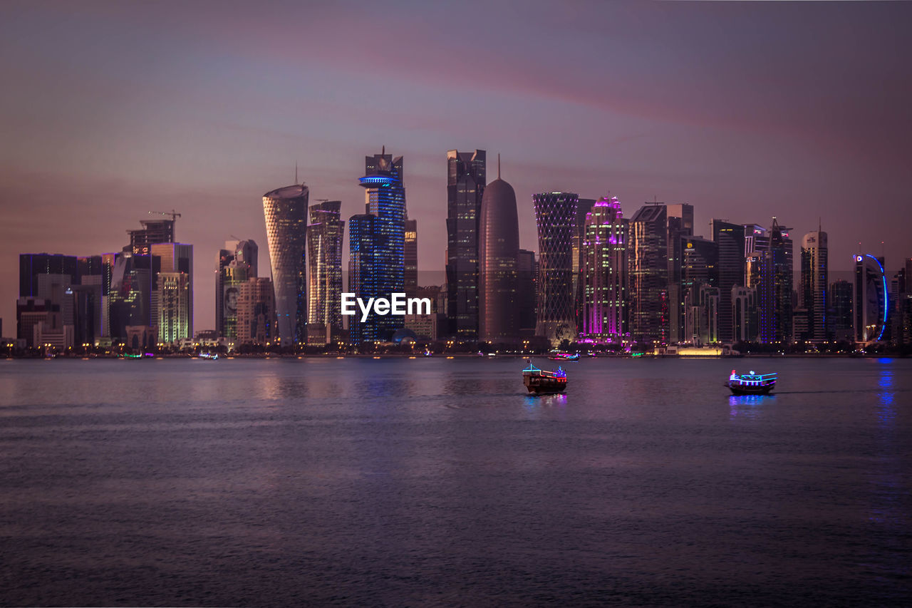 building exterior, architecture, built structure, city, building, sky, illuminated, water, waterfront, office building exterior, urban skyline, landscape, cityscape, skyscraper, transportation, sea, nature, tower, nautical vessel, tall - high, modern, no people, outdoors, financial district