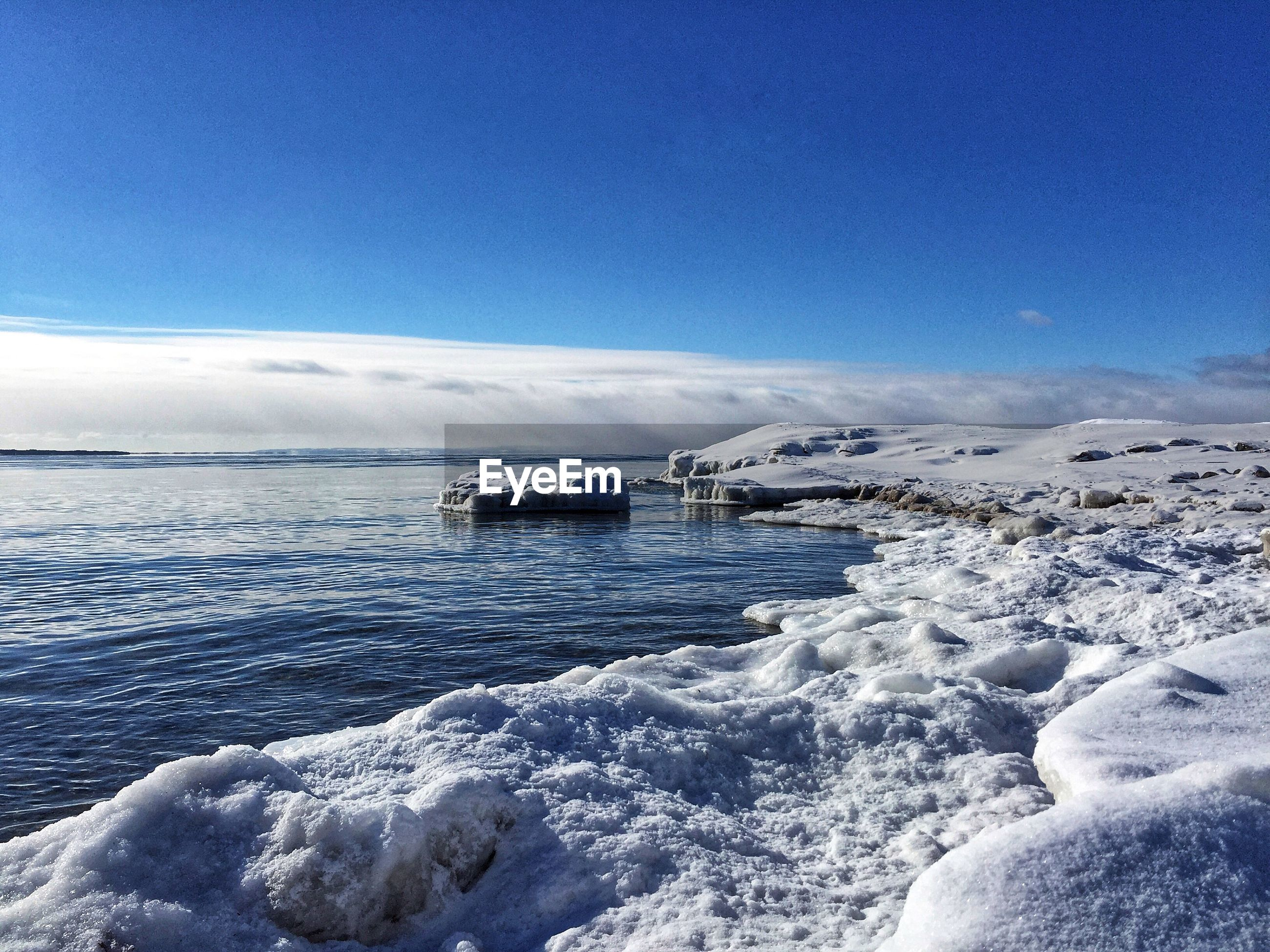 SCENIC VIEW OF SEA AGAINST BLUE SKY DURING WINTER