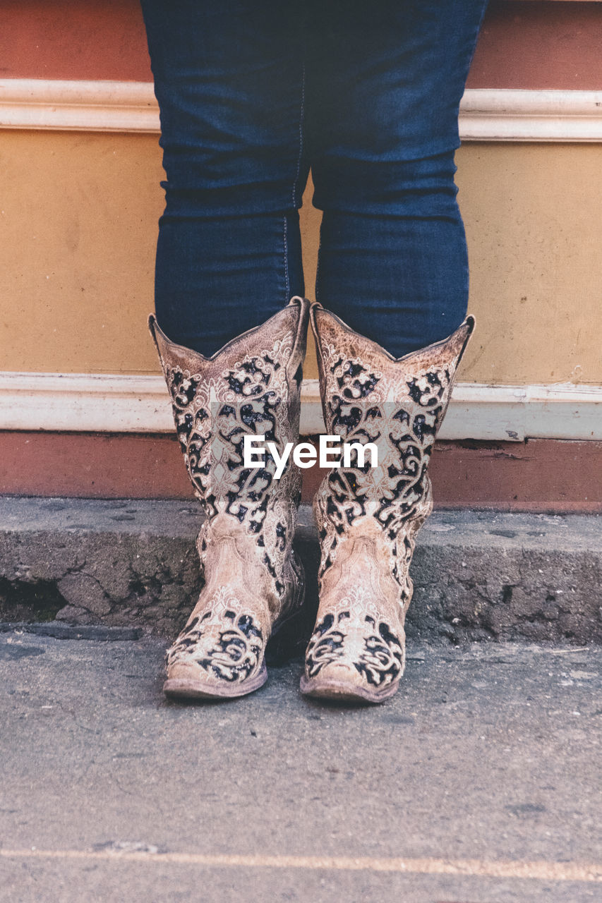 Low section of woman wearing cowboy boots standing against wall